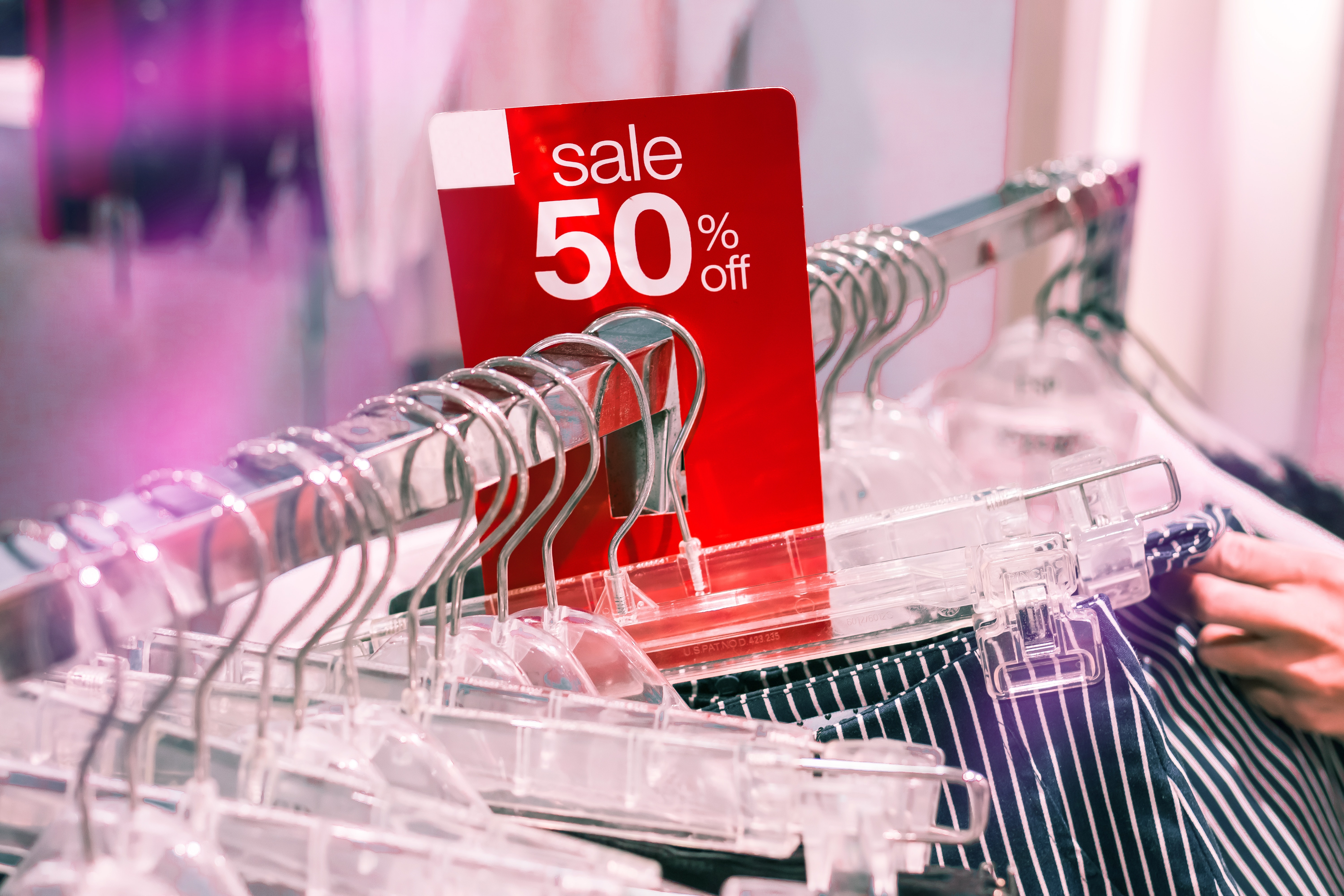 50% off sale sign on clothing at store
