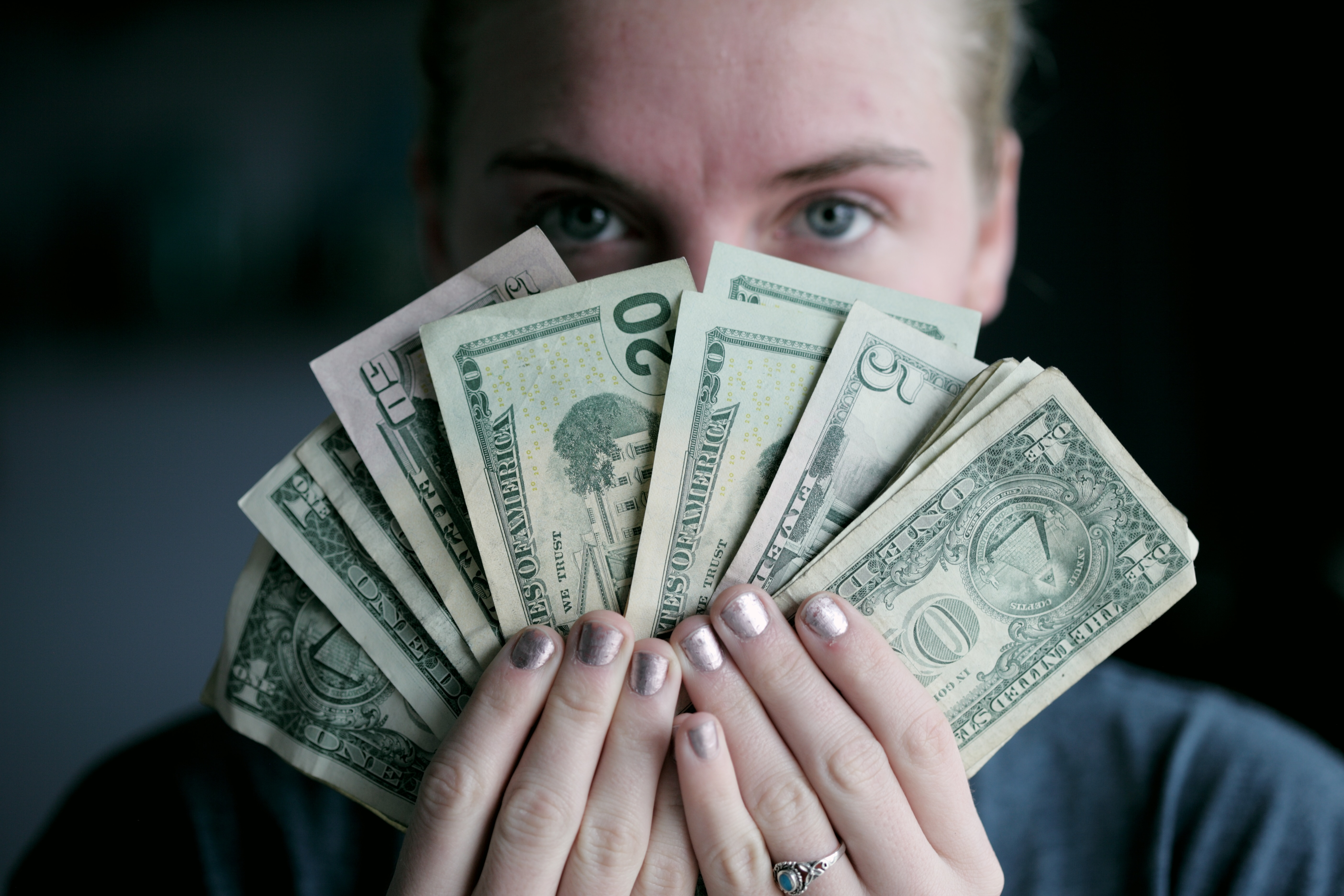 person holding fanned out money before their face