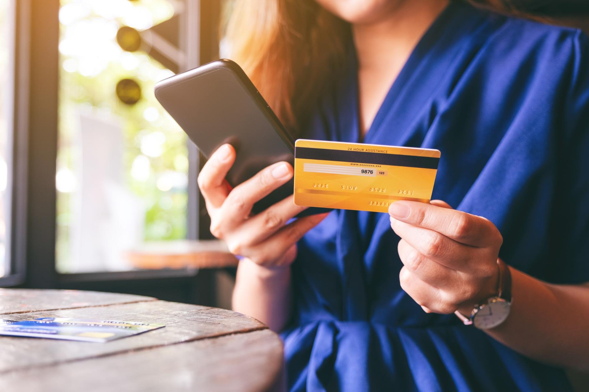 what is a good apr: woman holding credit card and phone