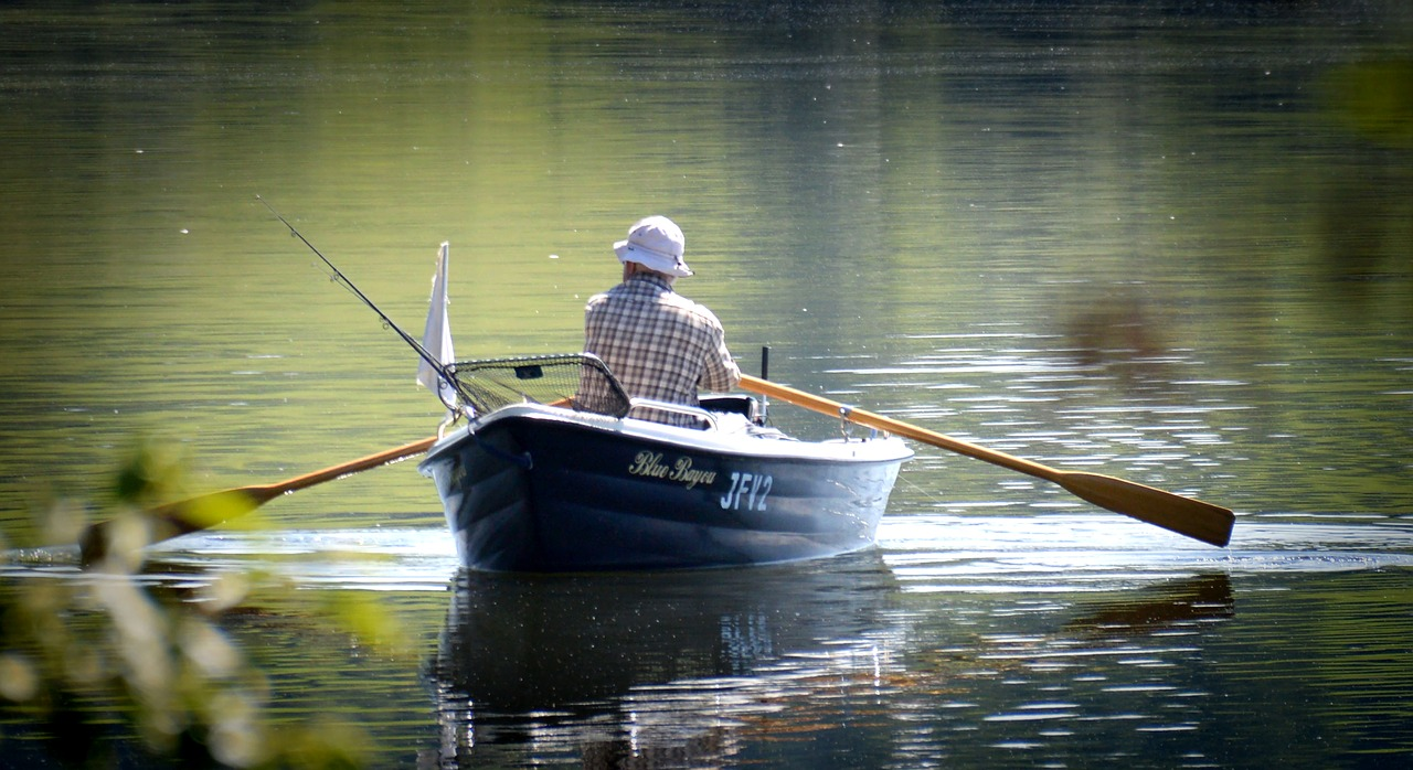 man rowing in fishing boat