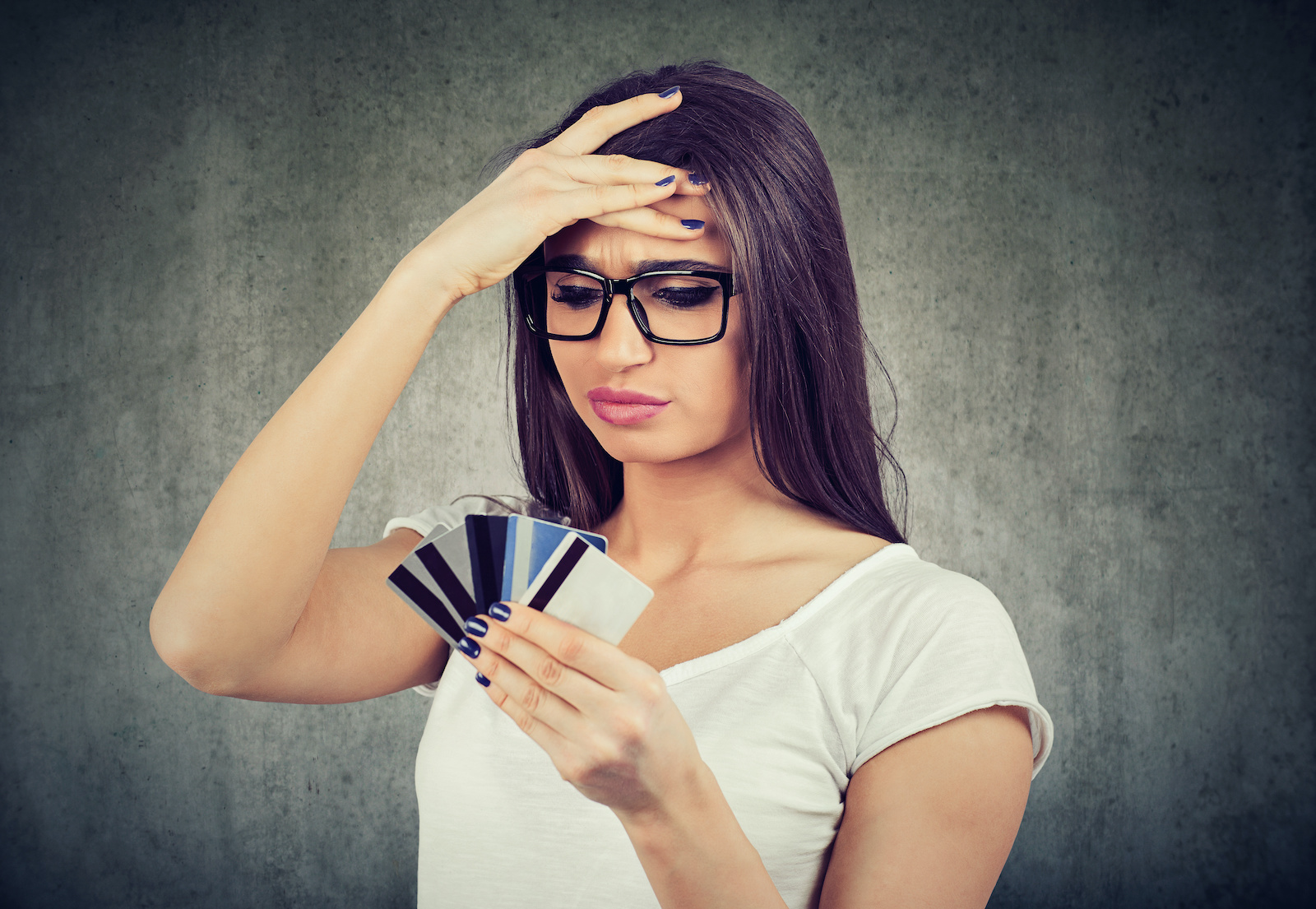 Best debt relief: Stressed woman holding multiple credit cards