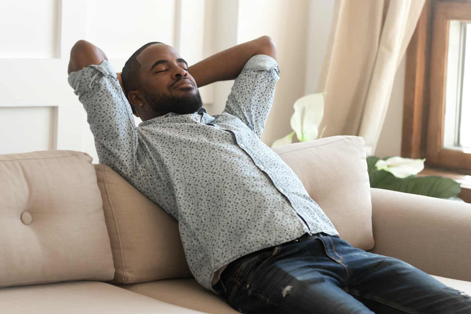 Best debt relief: A man leaning back, relaxing on the couch