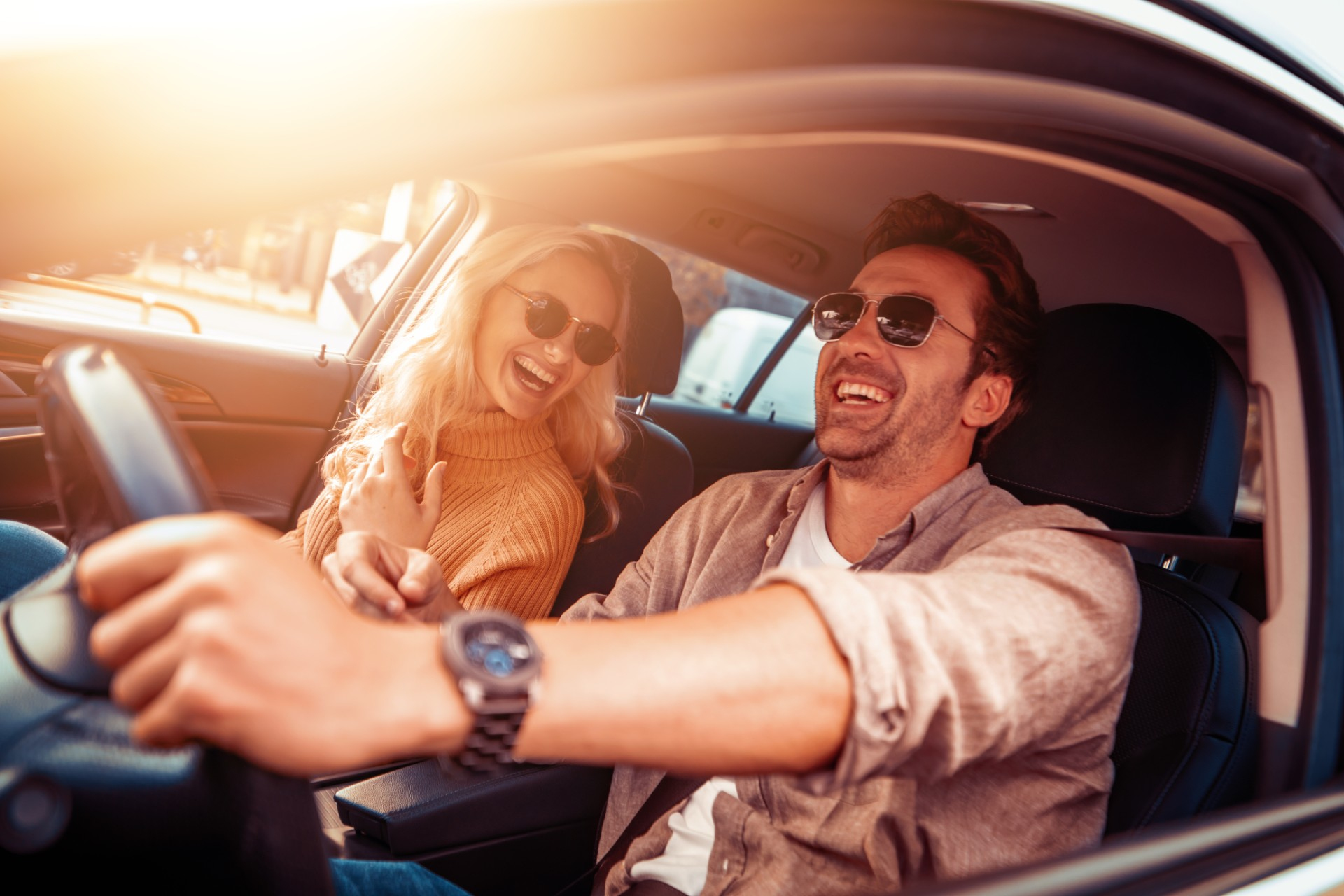 Smiling couple in a rental car