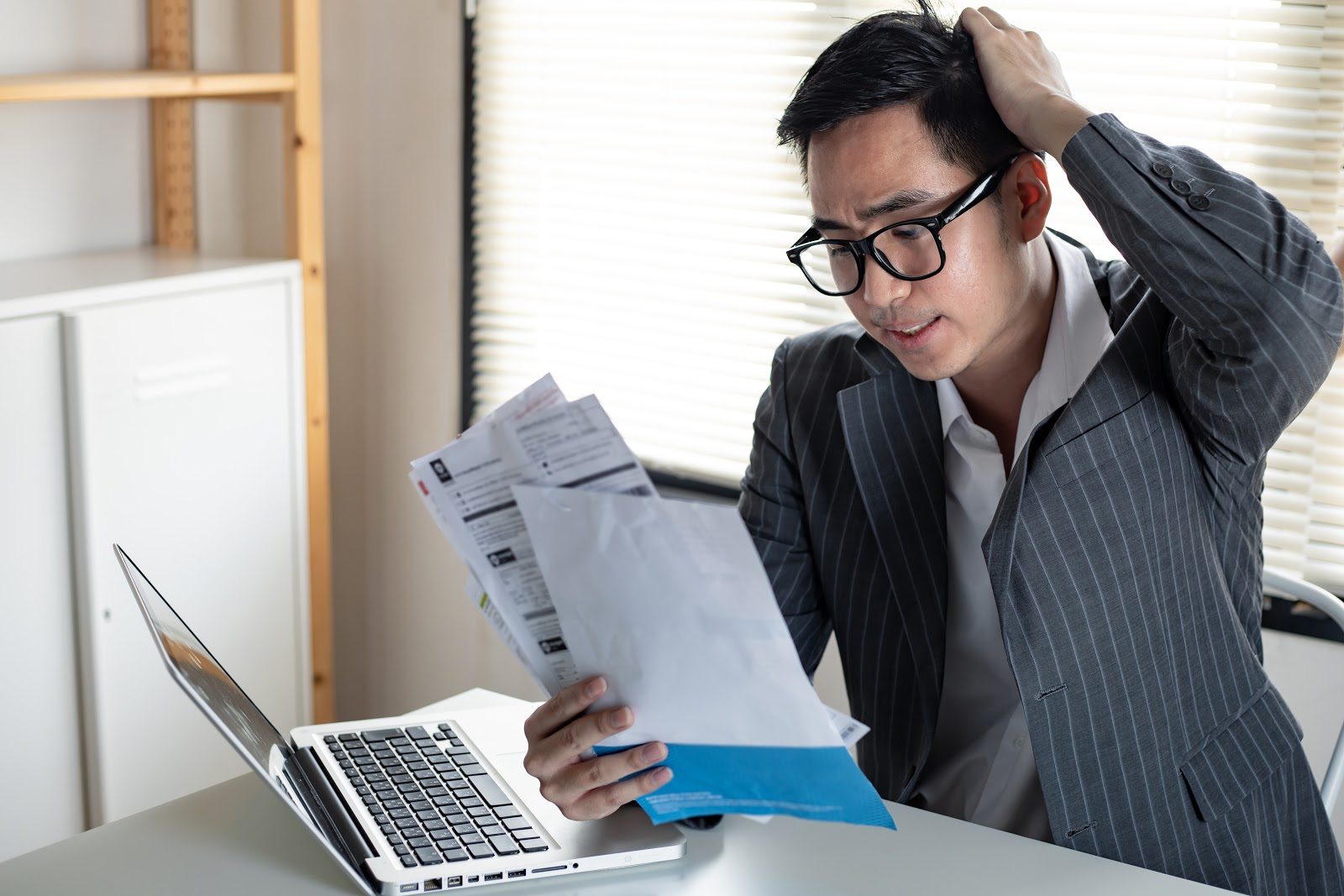 Credit card hardship program: Confused man looking at bills