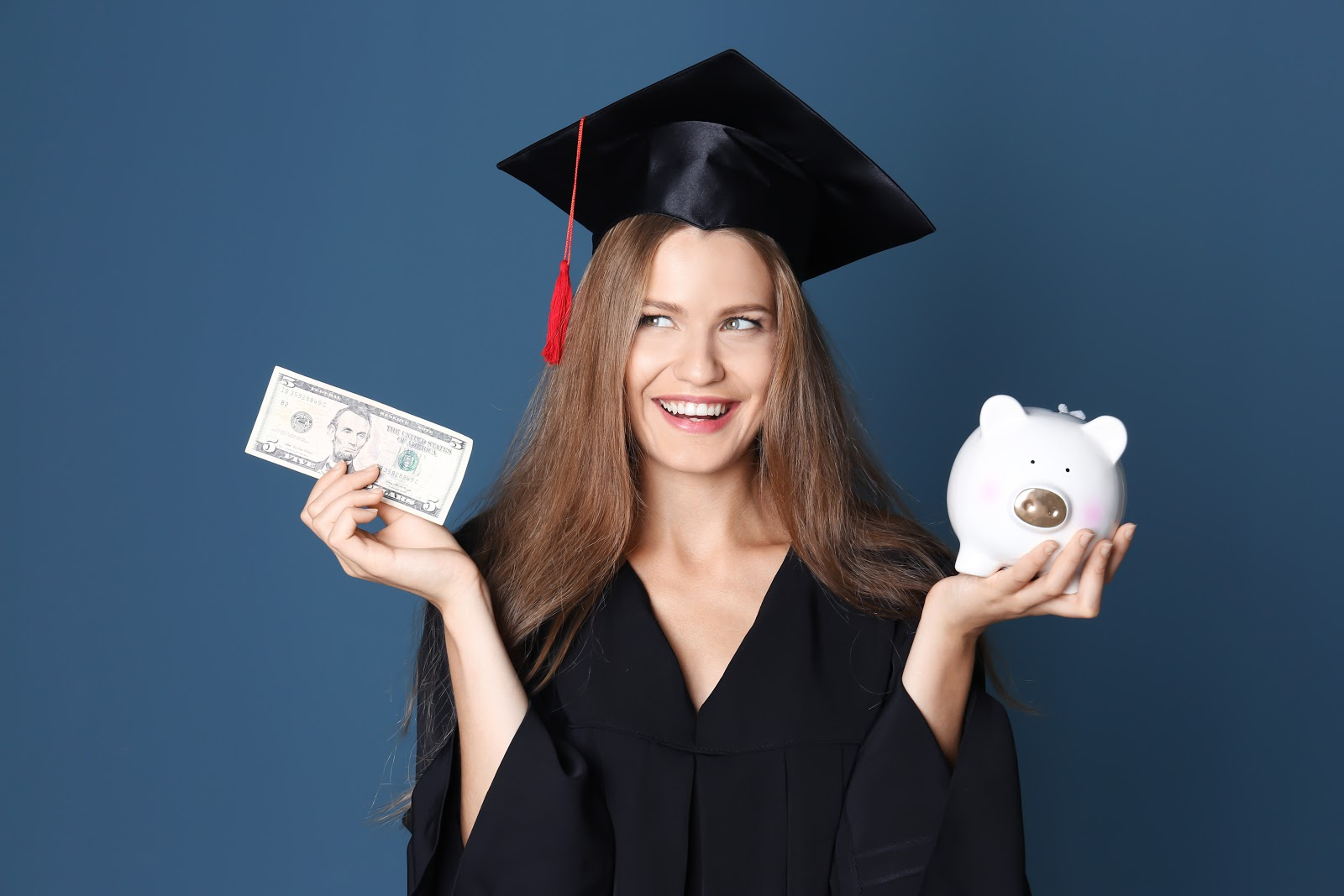 Young graduate with piggy bank hoping for debt forgiveness