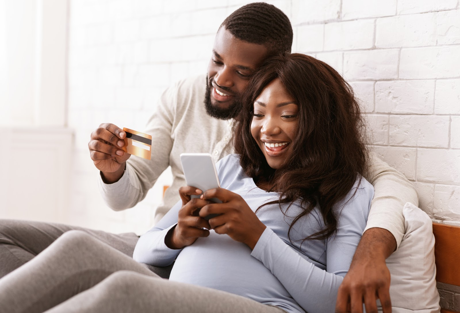 Happy expectant couple reviewing how to pay off debt