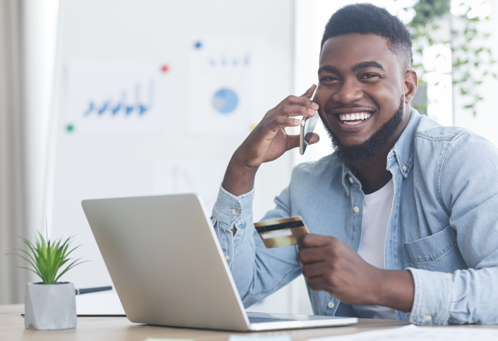 Smiling man on phone while using his credit card to shop online
