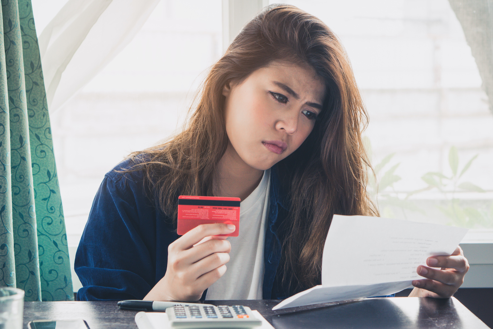Credit card debt consolidation: A woman holds her credit card and looks at her bill