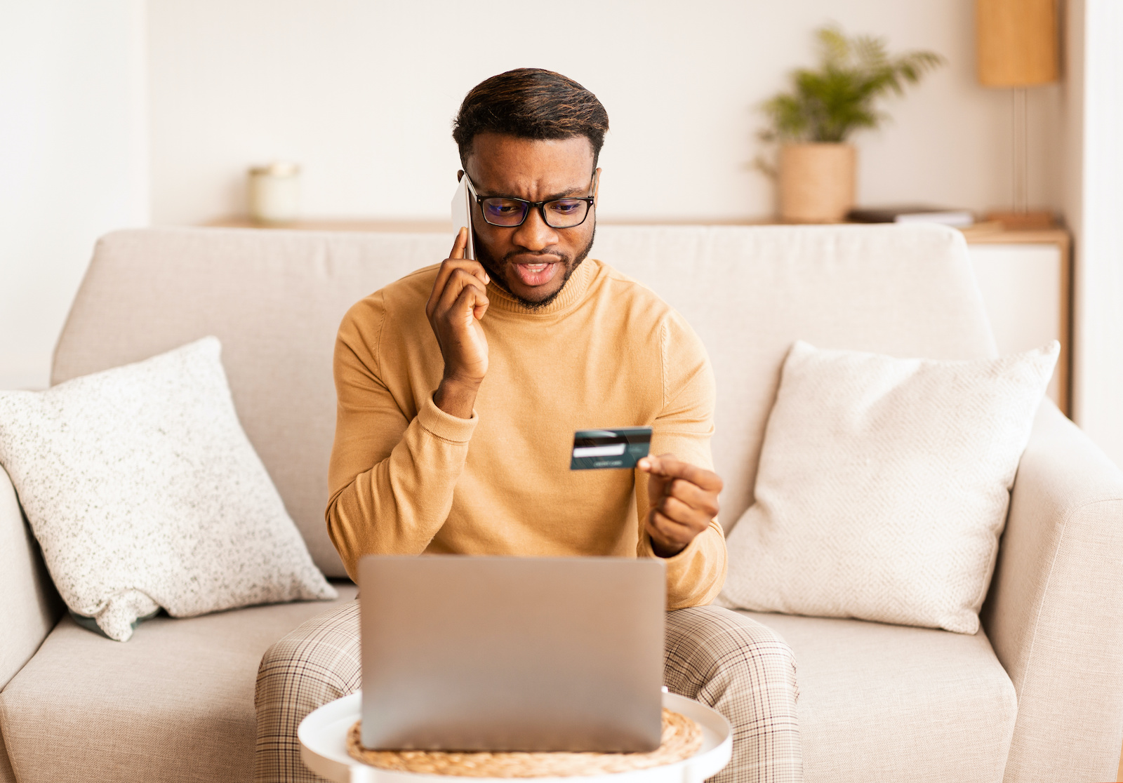 Credit card debt relief: A man holds his credit card, looks at his laptop screen, and talks on the phone