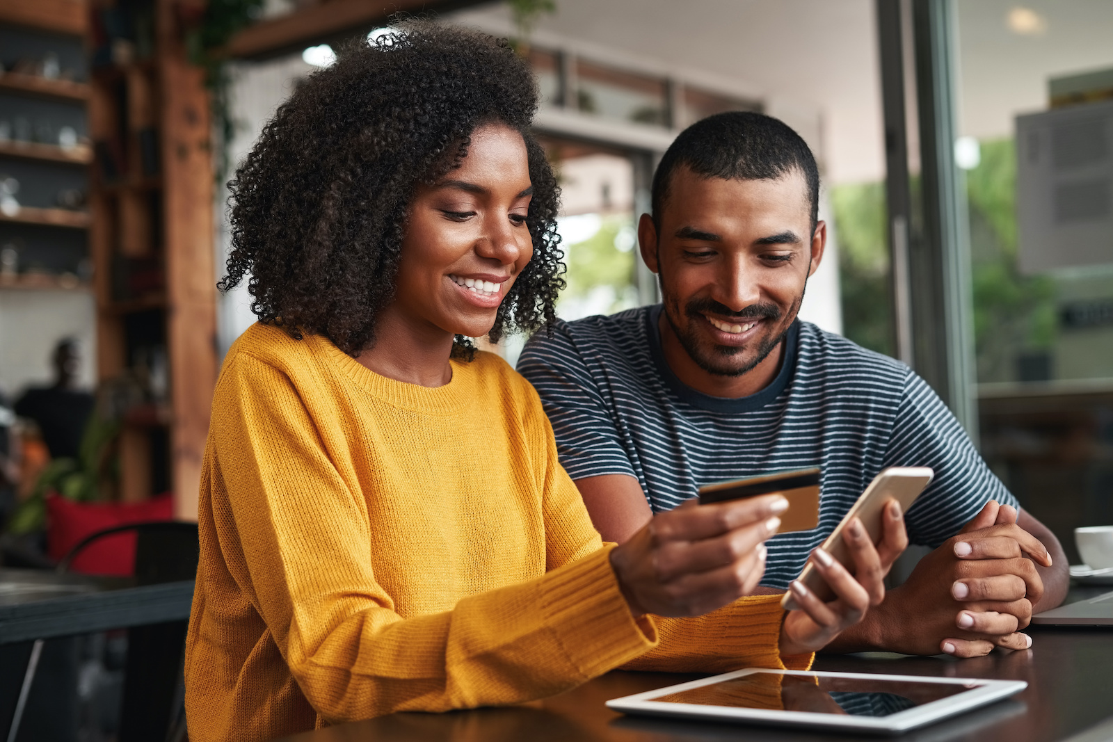 Credit card debt relief: A happy couple hold a credit card and check their balance on a phone