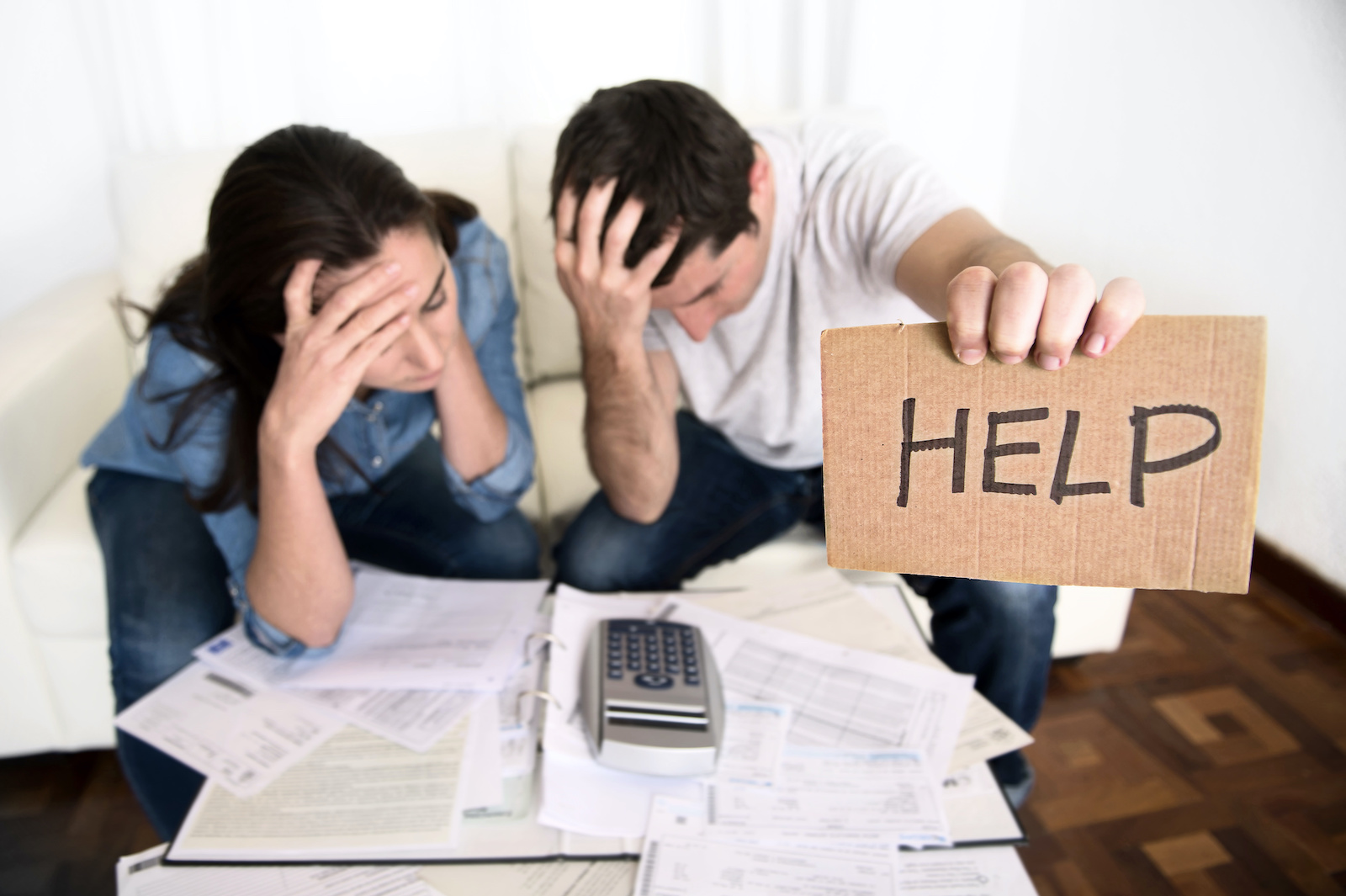 """Debt Consolidation Loans for Bad Credit: A young couple looks at their bills and holds up a sign that says """"HELP"""""""