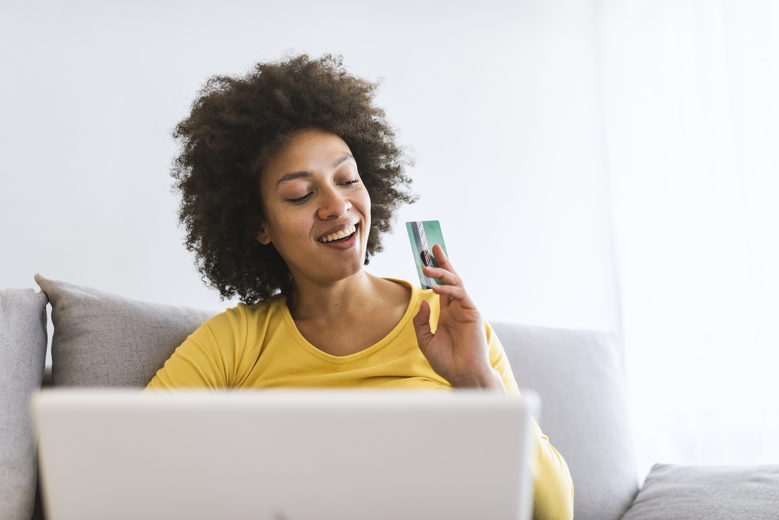How long will it take to pay of my credit card: A woman at her computer smiles and looks at her credit card