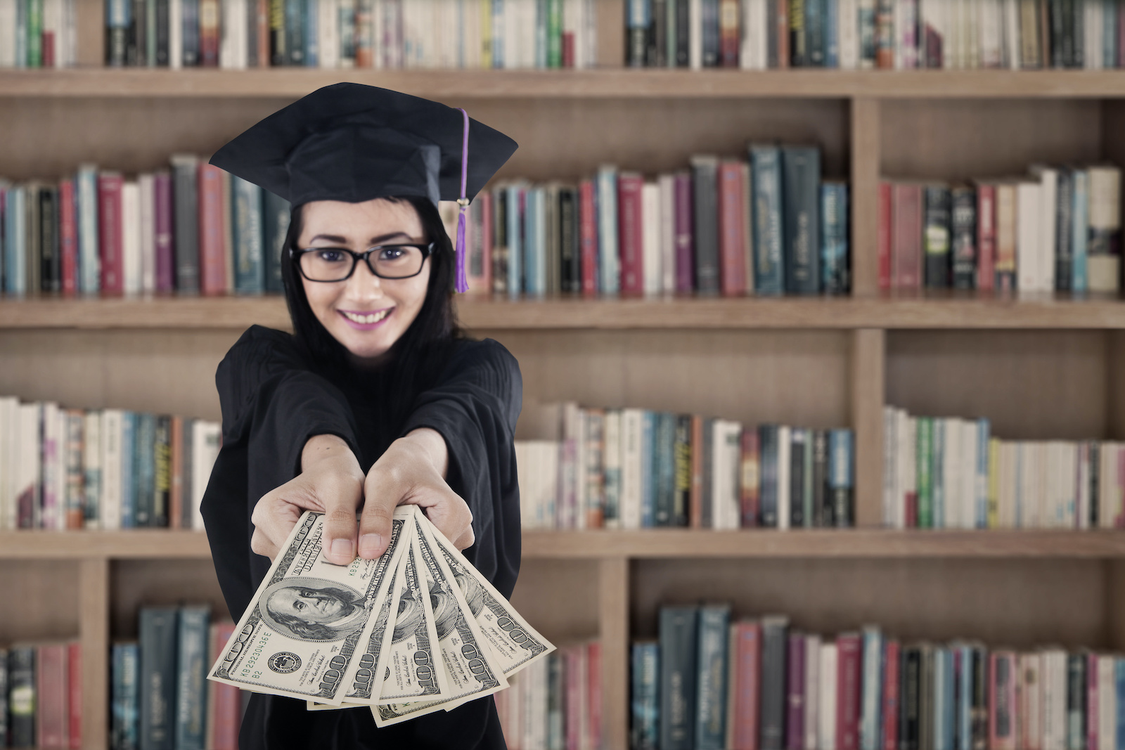 Subsidized vs unsubsidized student loans: A college grad holds hundred dollar bills in her outstretched hands