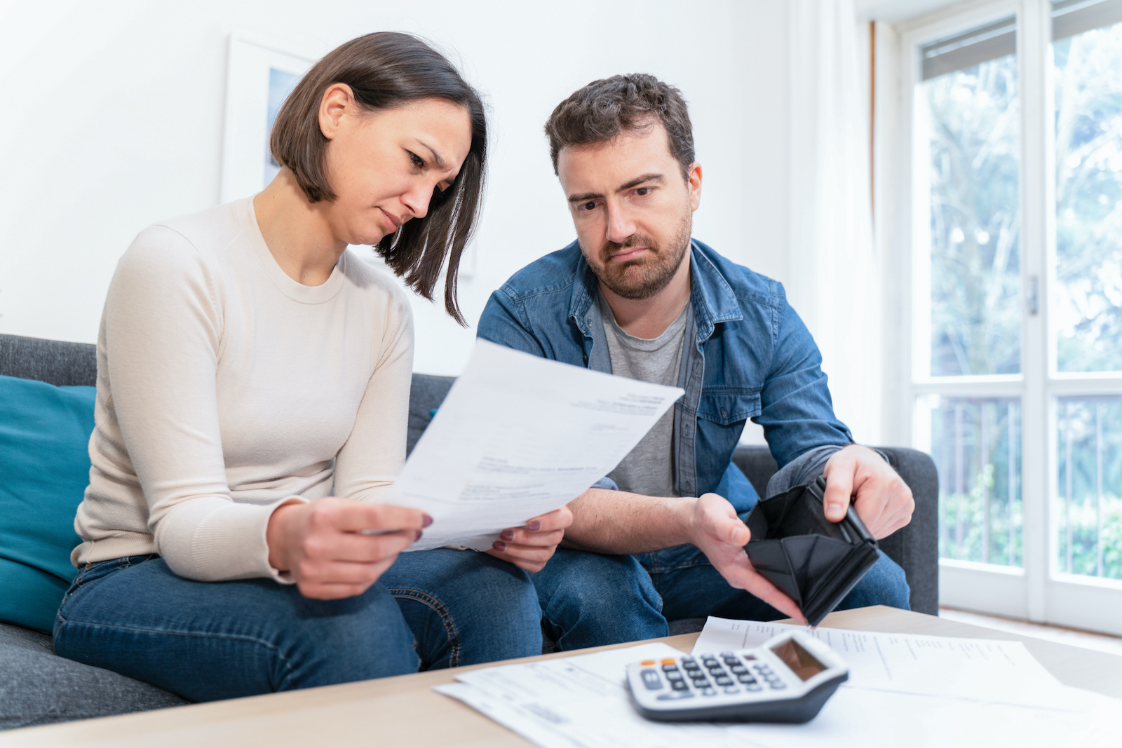 Do you have to pay back unemployment: A worried couple checks their payment information with a calculator