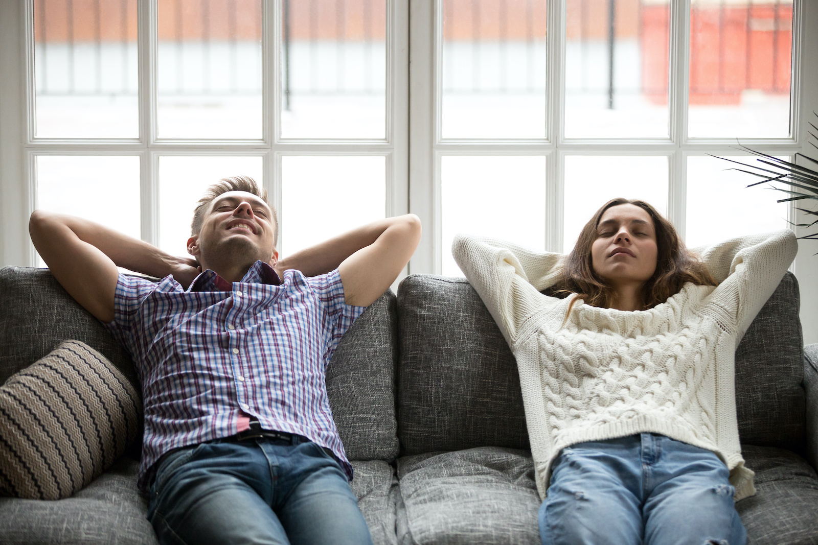 How does debt consolidation work: A couple sits back, relaxed on their couch