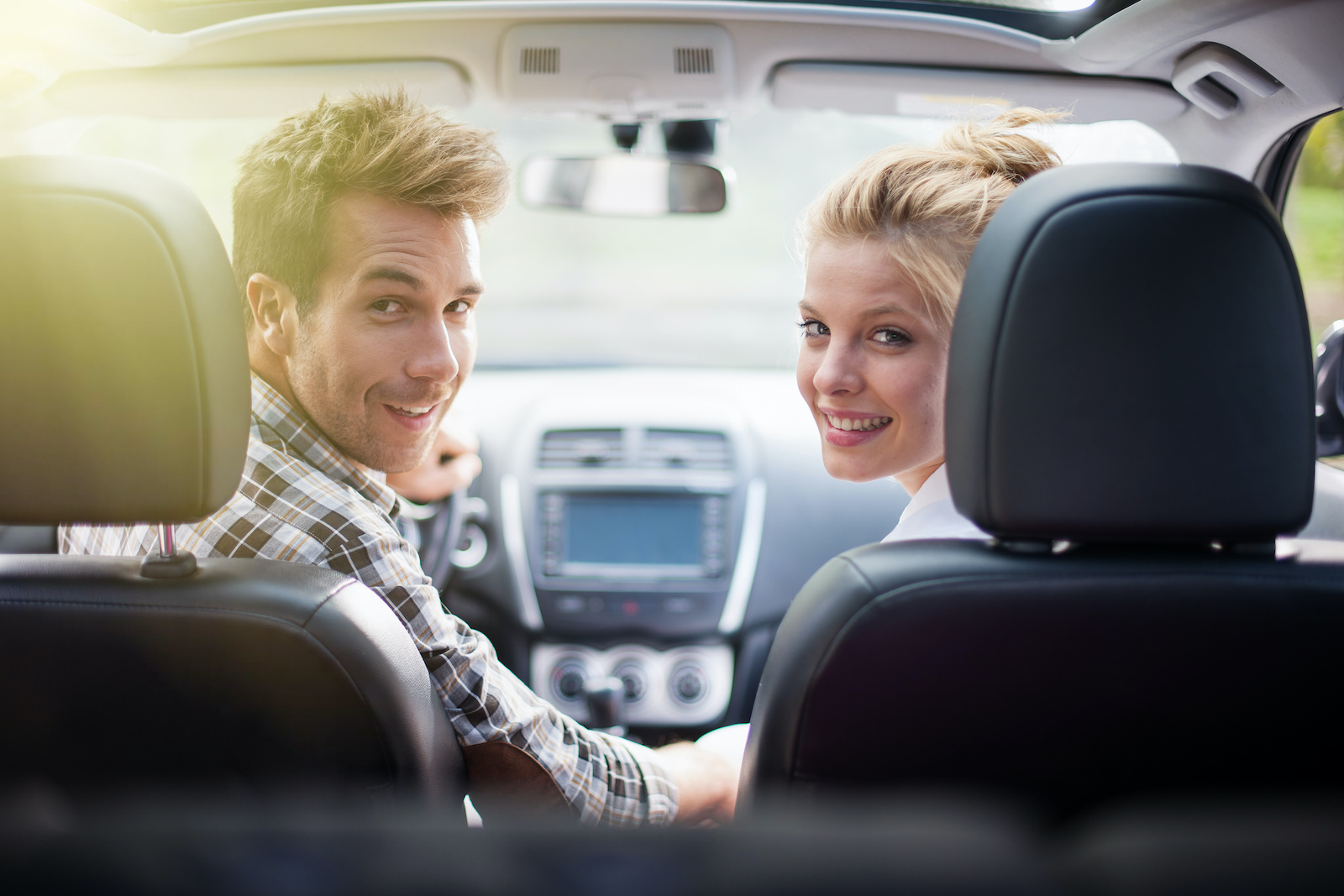 How to build credit without a credit card: A young couple looks back from the front seat of their new car after having secured an auto loan