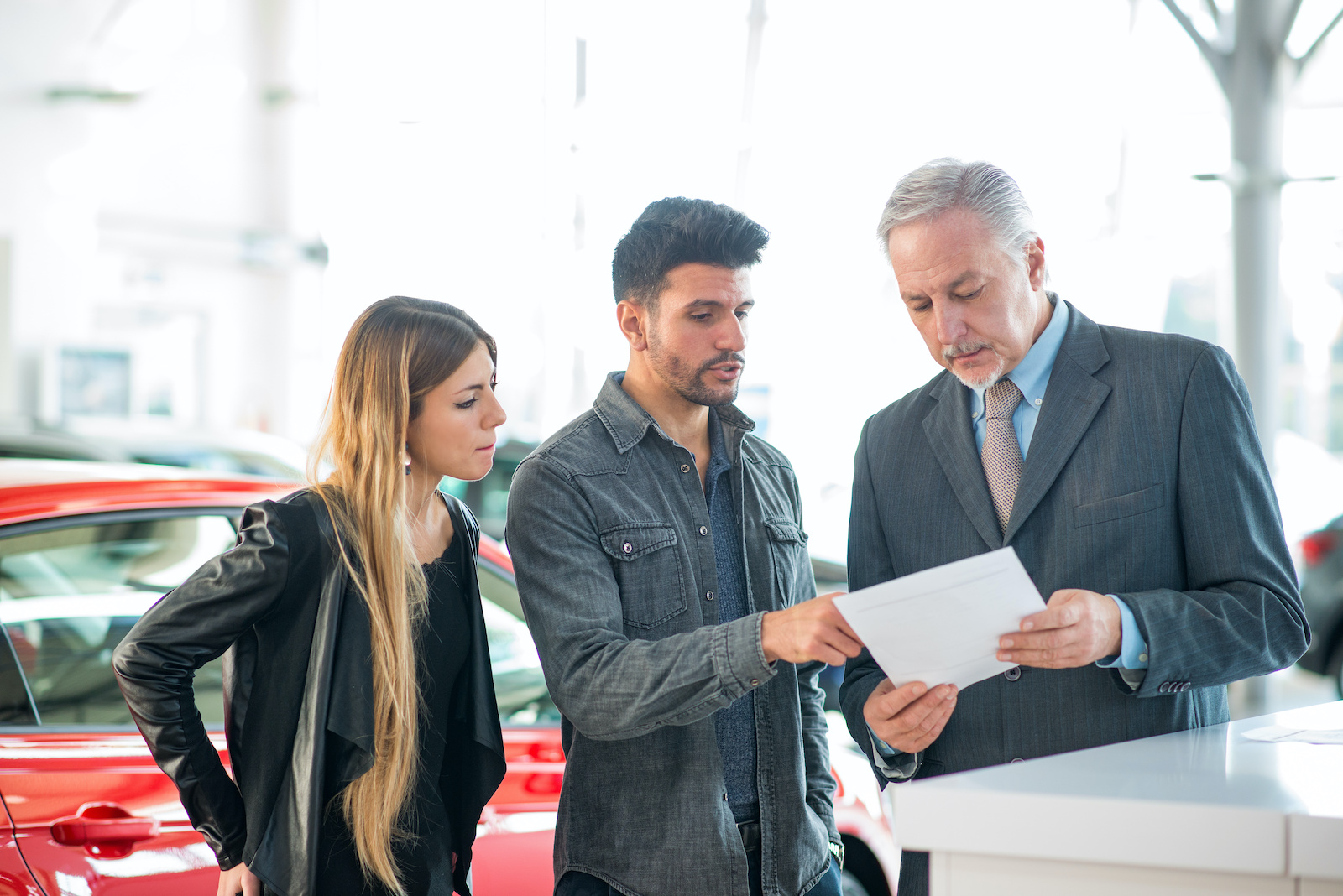 Installment loans for bad credit: A young couple looks at auto loan terms at a car dealership