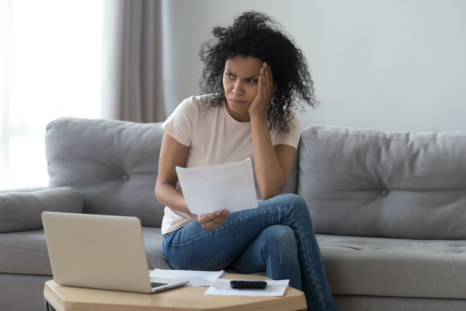 Installment loans for bad credit: A stressed woman looks at paperwork and her computer
