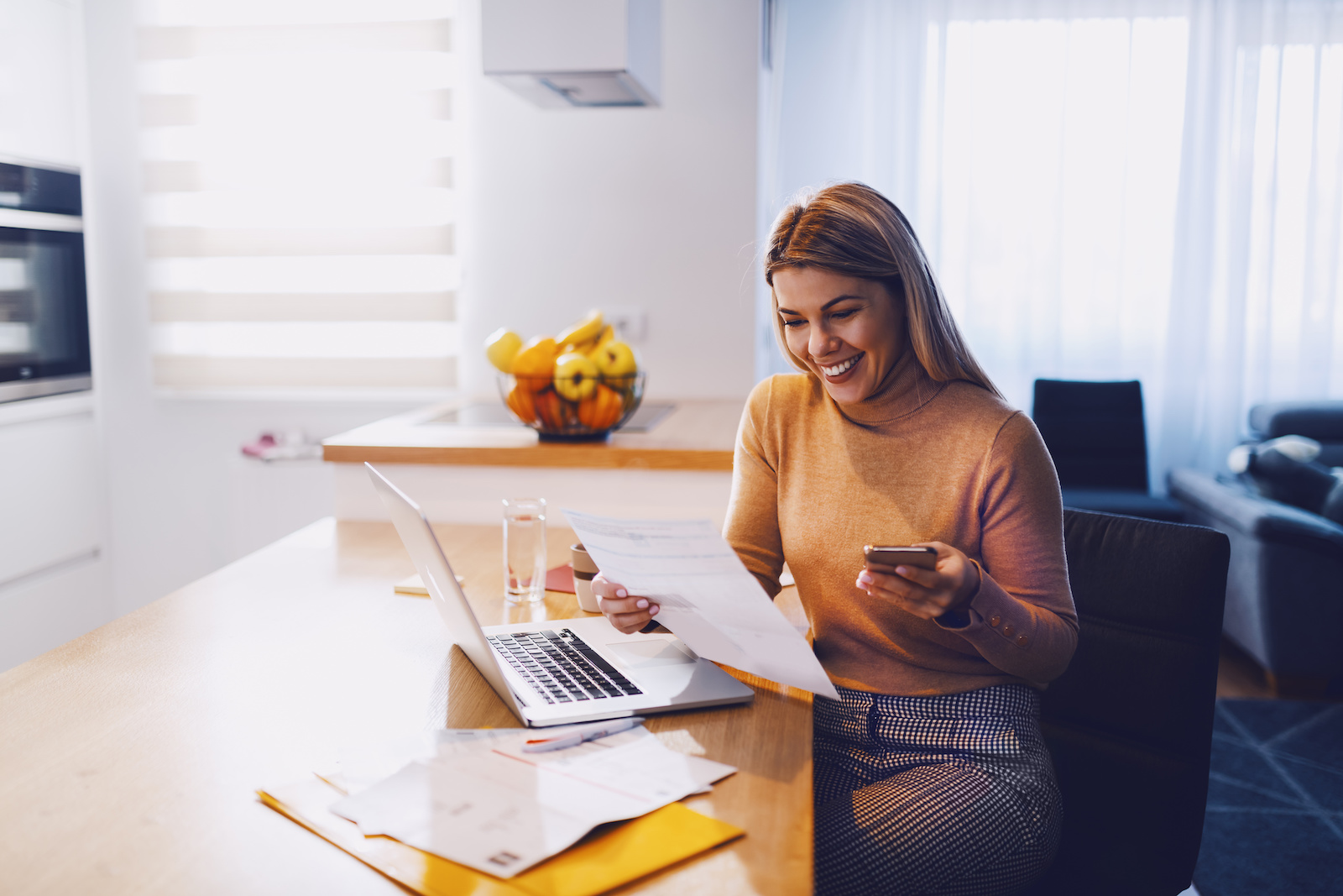 Soft credit check: A smiling woman looks at a financial document