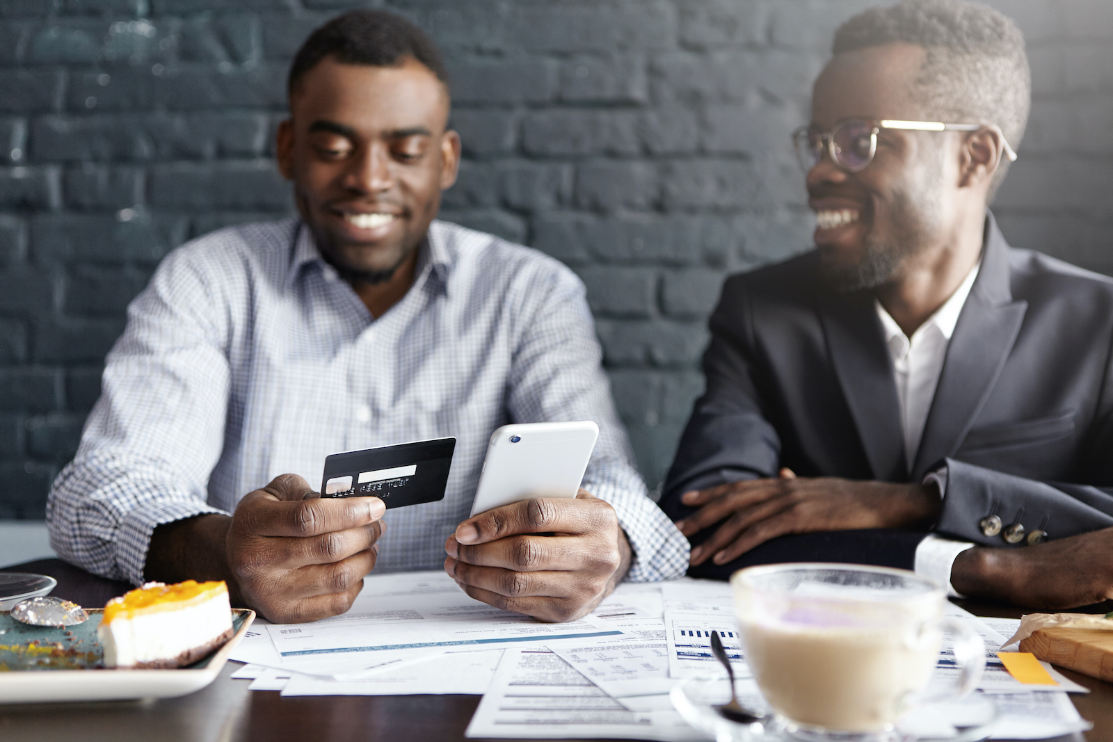 The best way to build credit: Two men look at a credit card and credit documents