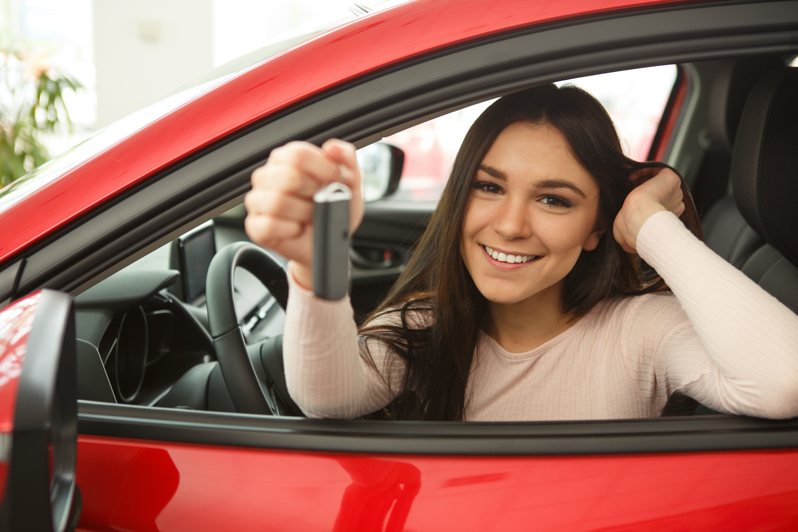 The best way to build credit: A smiling woman holds the keys to her new car