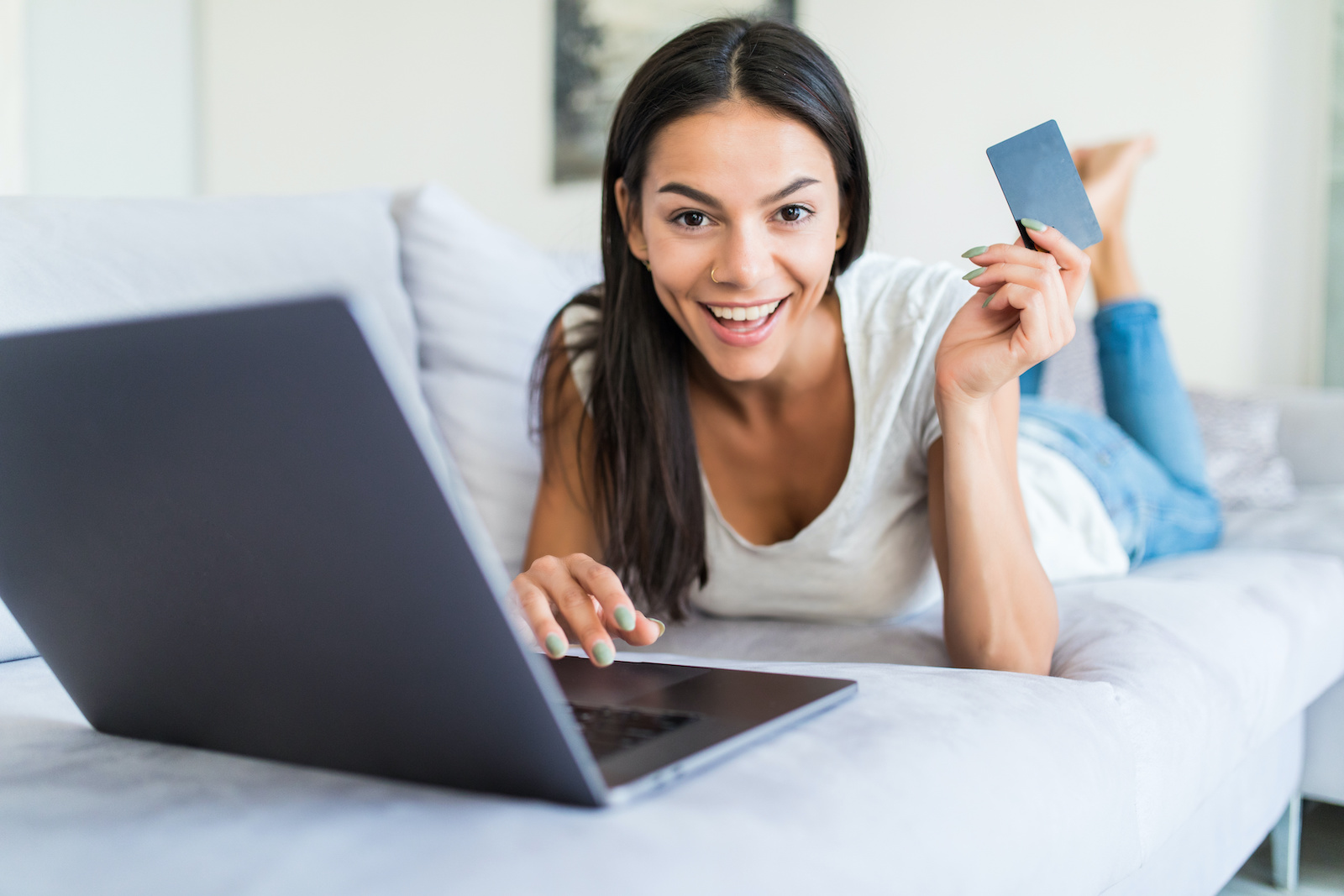 Credit card for bad credit: A smiling woman holds a credit card while working on the computer