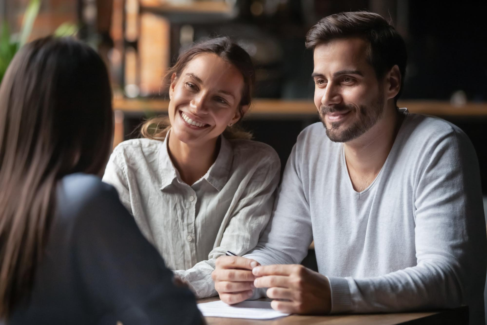 Couple smiles at woman they are meeting with