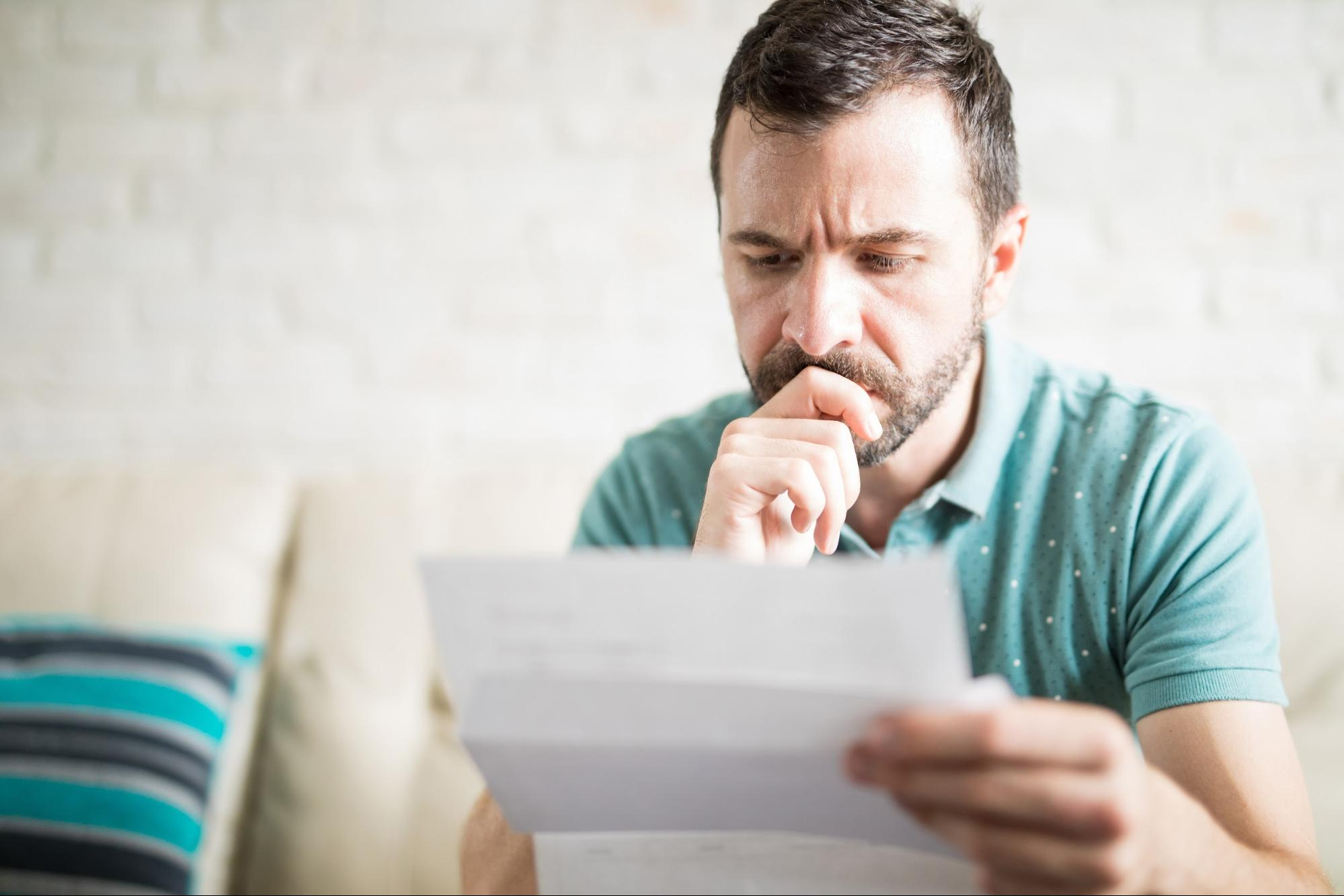 Man looks at piece of paper with worried look