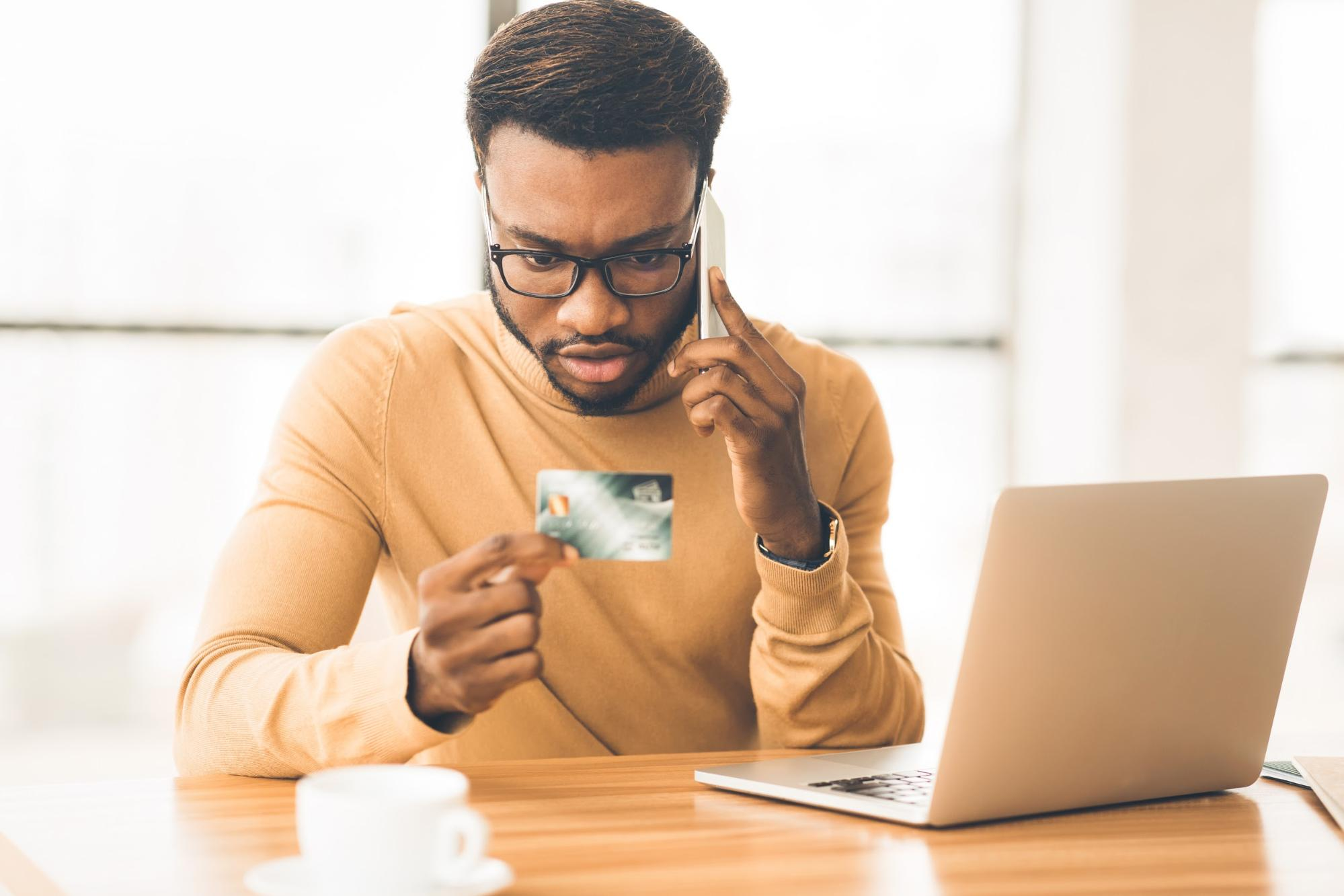 Credit card debt calculator: Man looks at credit card while talking on phone