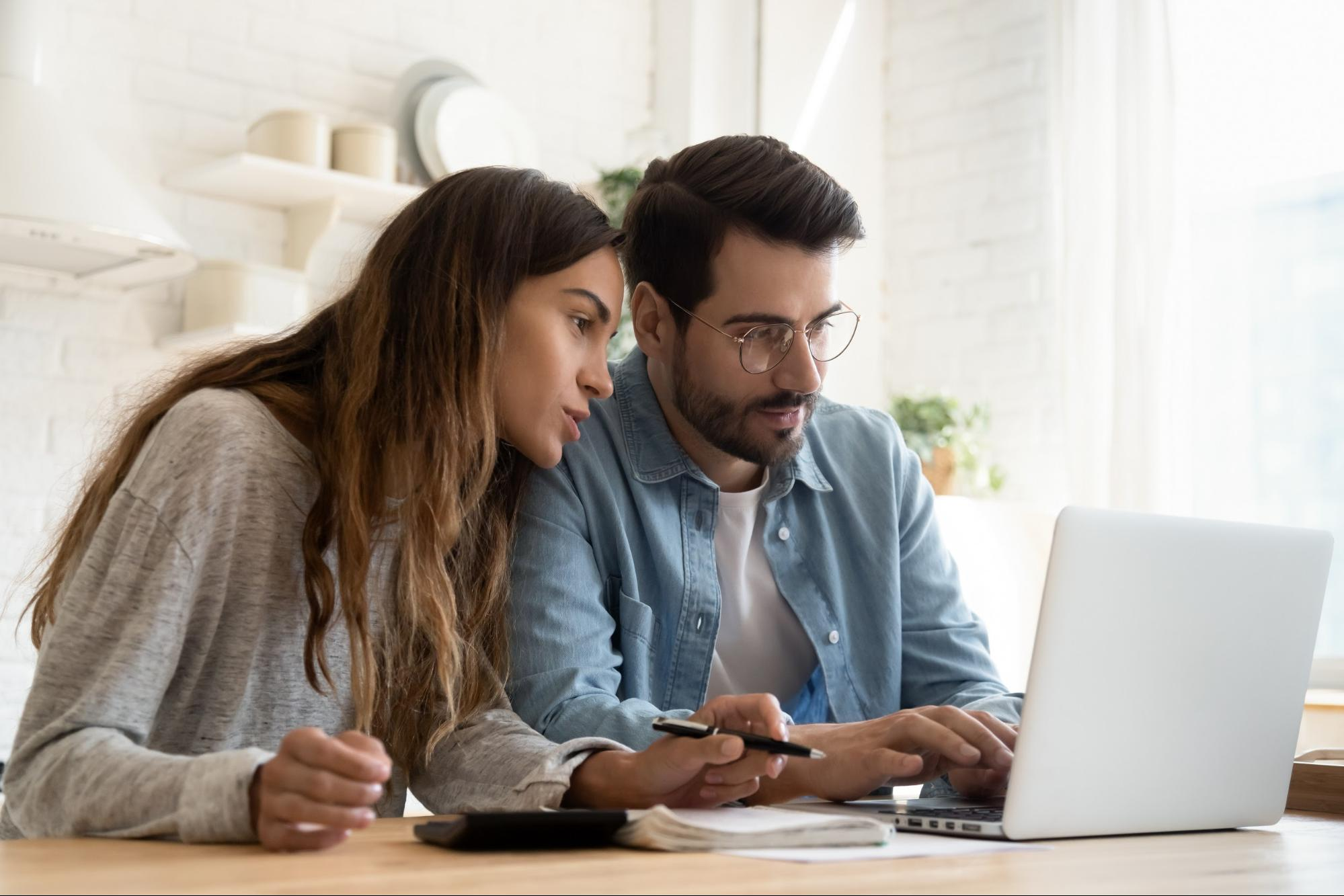 Couple looks at laptop together