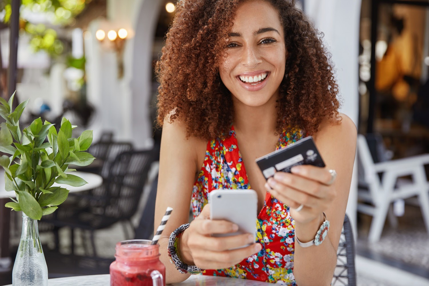 Low interest credit cards: Young smiling woman holding credit card while sitting at a cafe