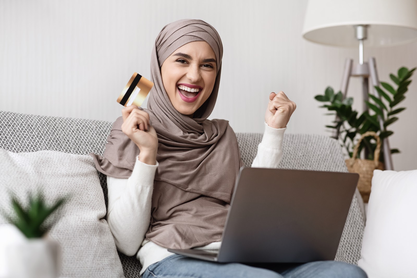 How to improve credit score in 30 days: Happy woman holding credit card