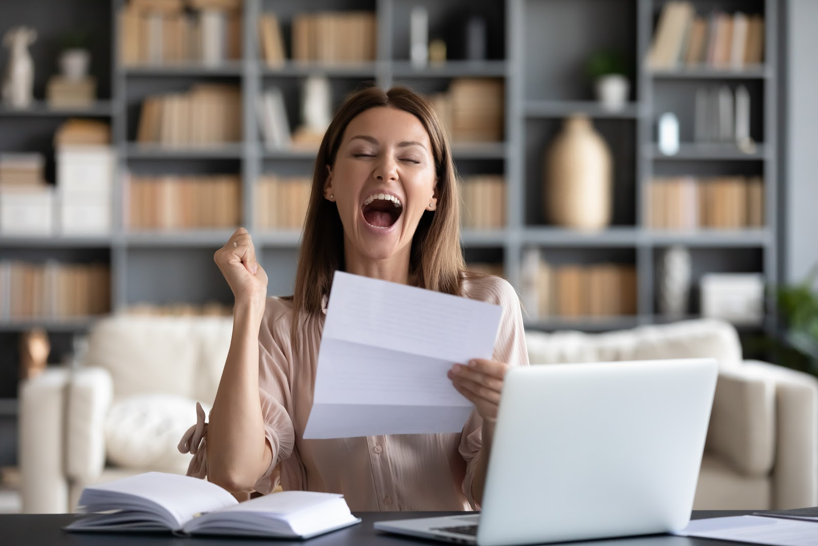 Joyful woman holding her good credit report