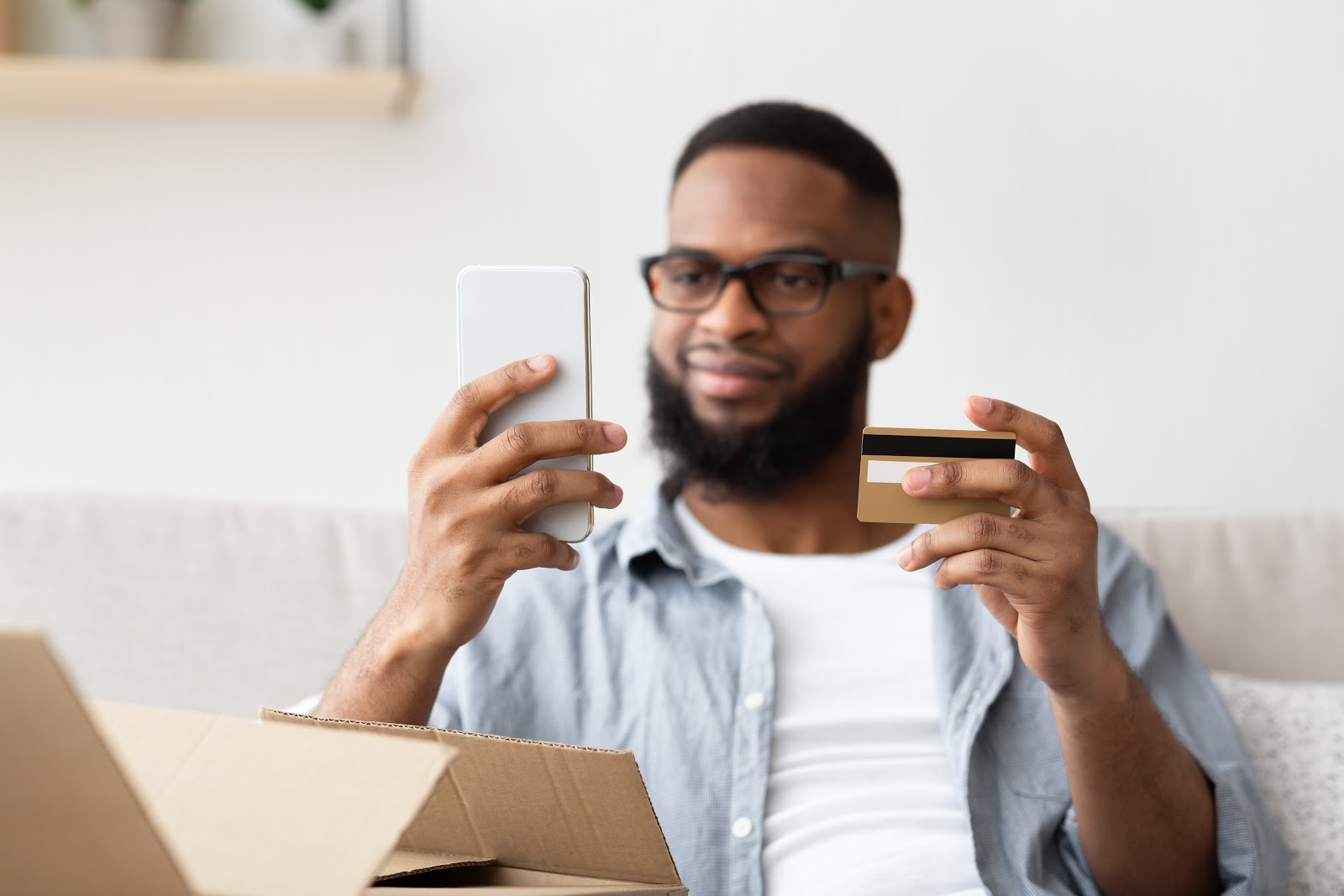 African American man with smartphone and credit card