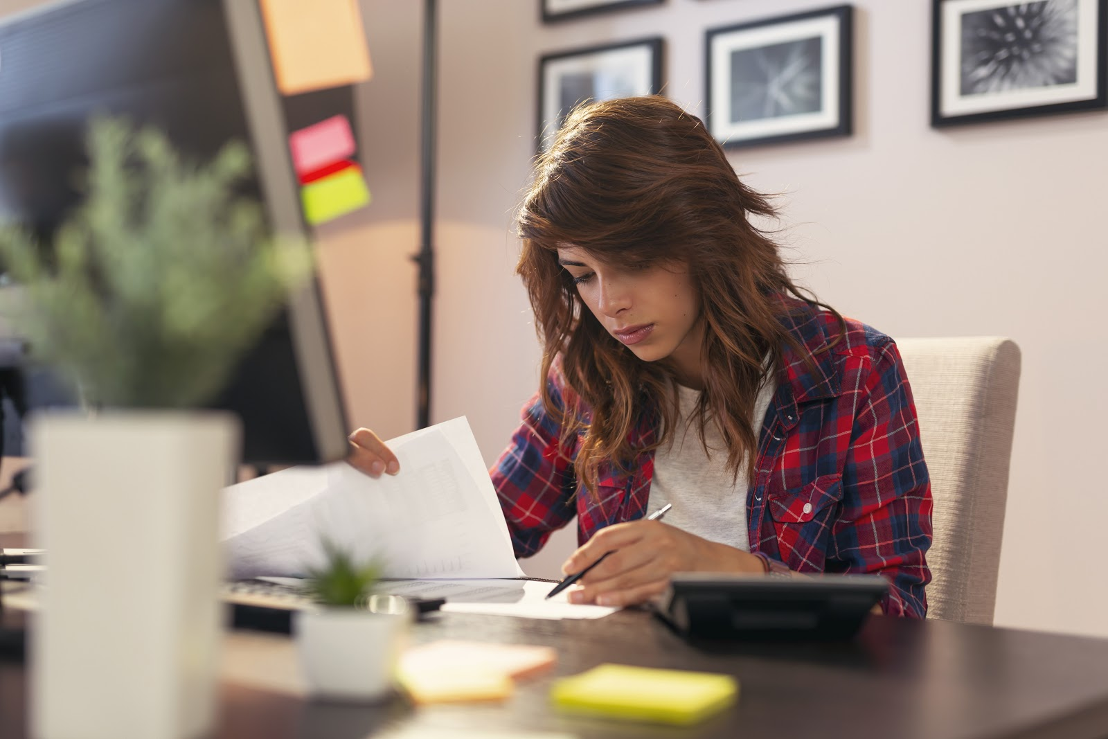 Young woman reviewing documents, working late in a home office
