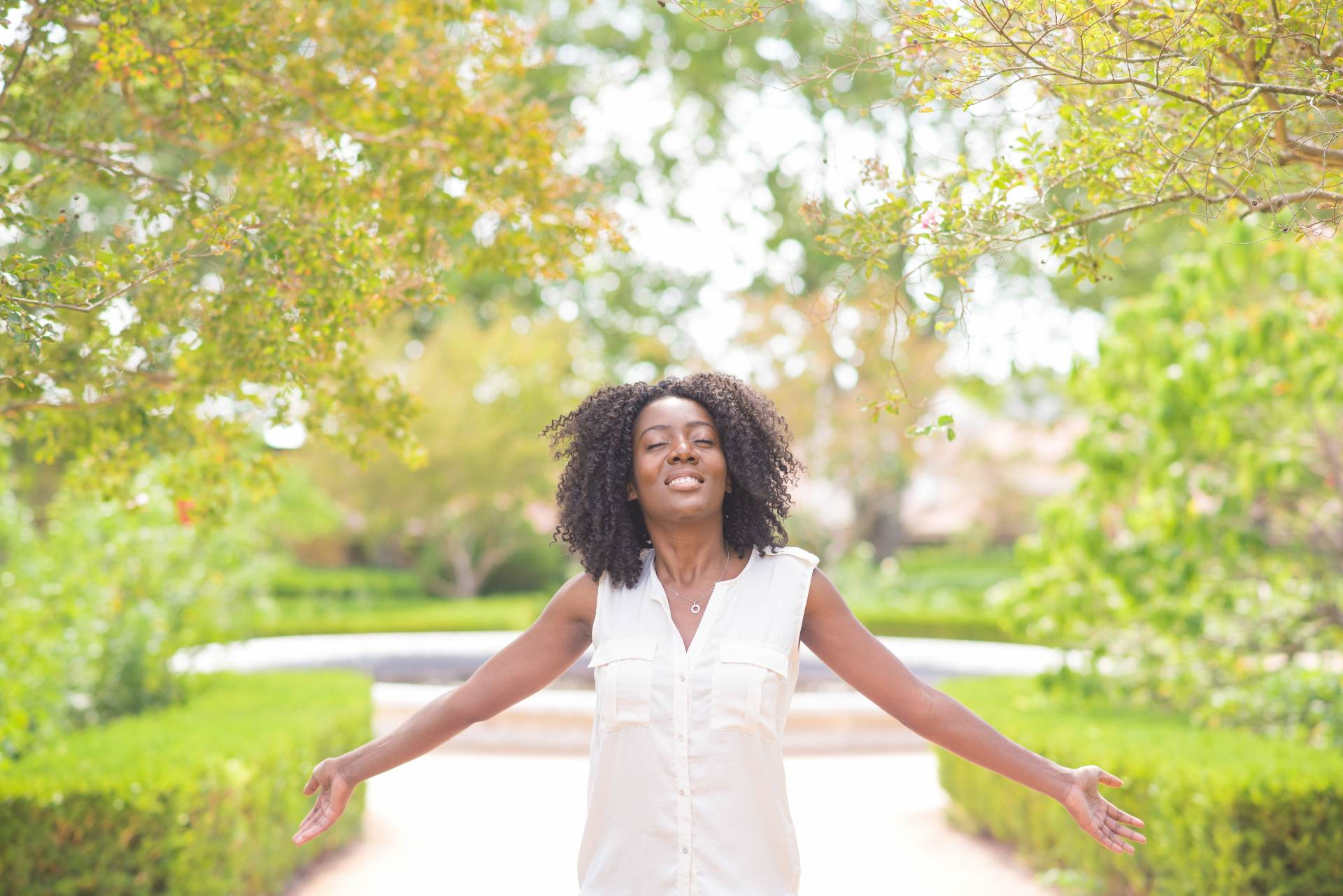 Smiling woman in a garden representing financial freedom
