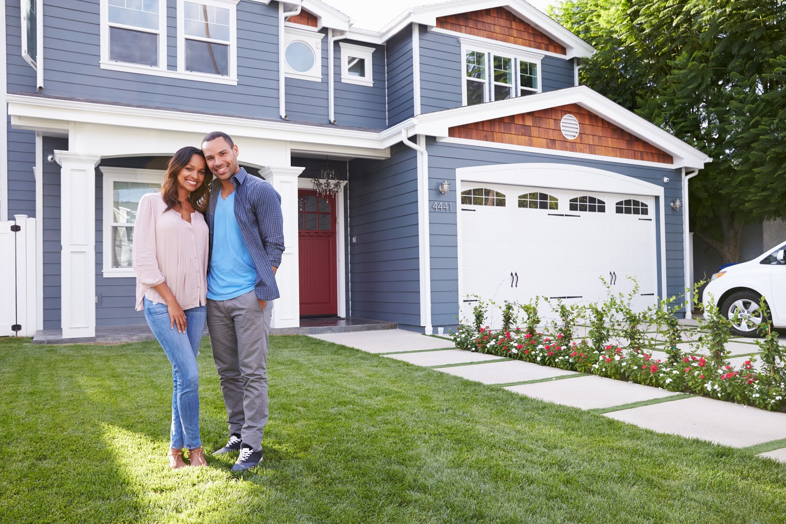 Happy couple standing in front of their new house
