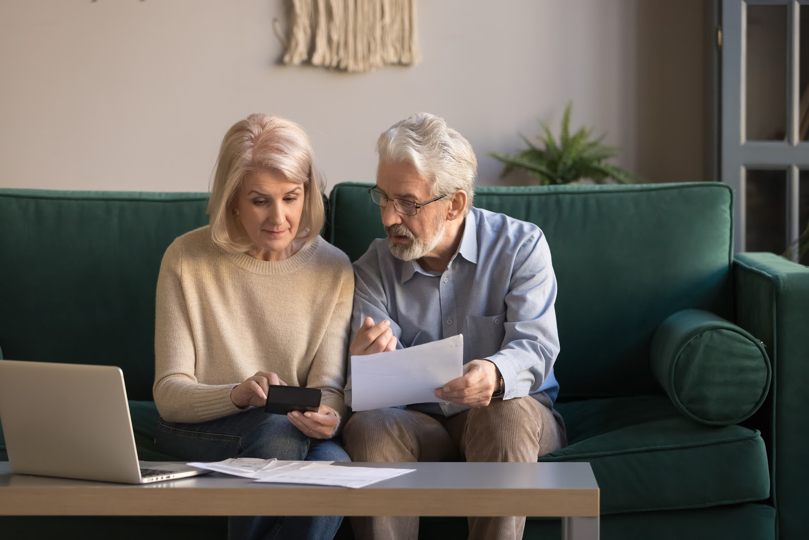 Debt snowball method: older couple reviewing finances