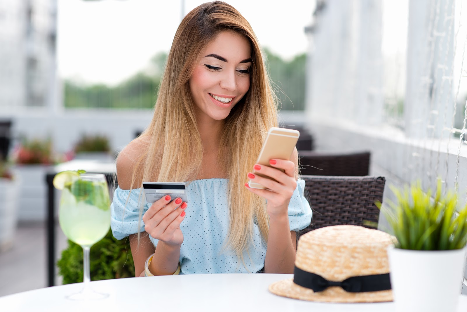 Smiling woman in a cafe holding a credit card and smartphone