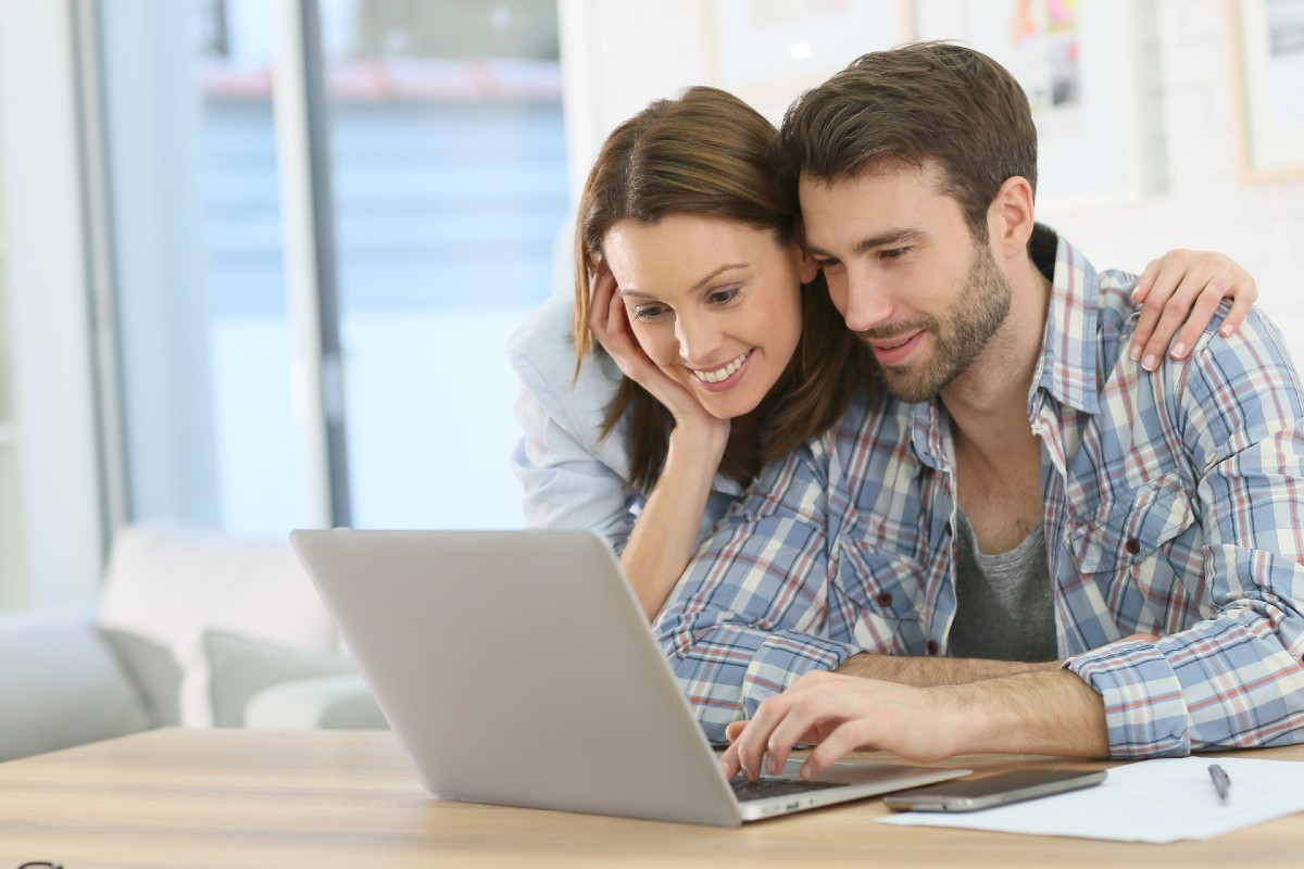 Couple with laptop reviewing best transfer cards for fair credit