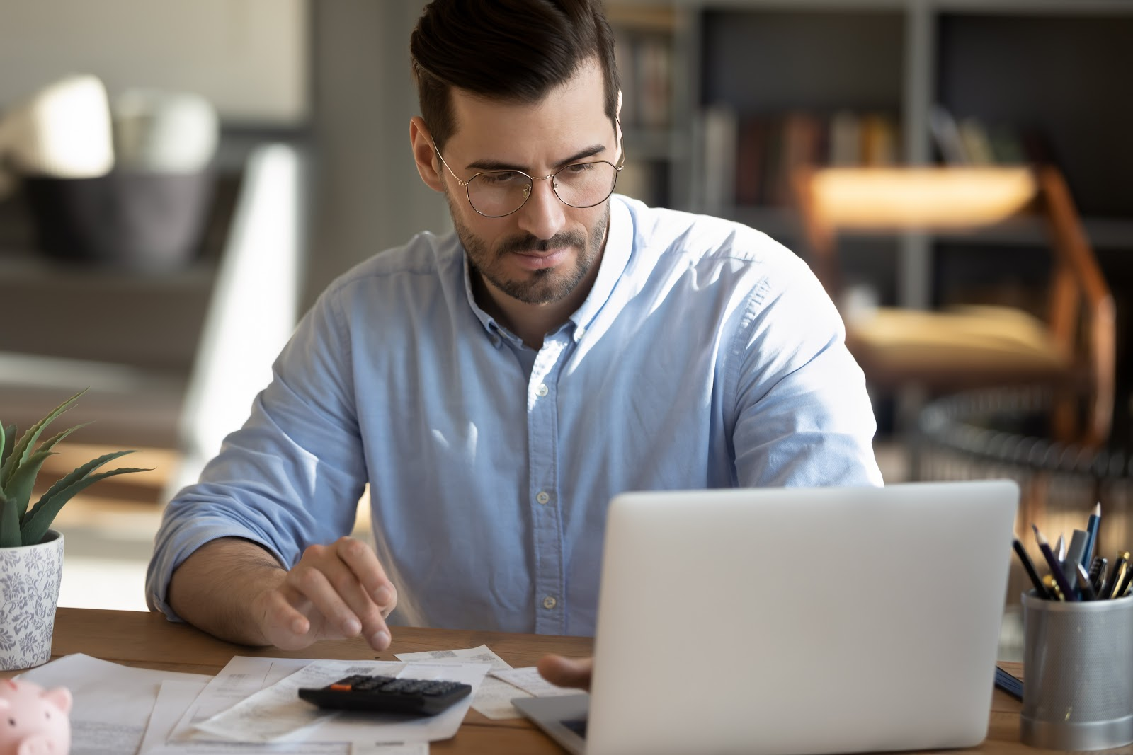 Focused young man at laptop working on financial matters