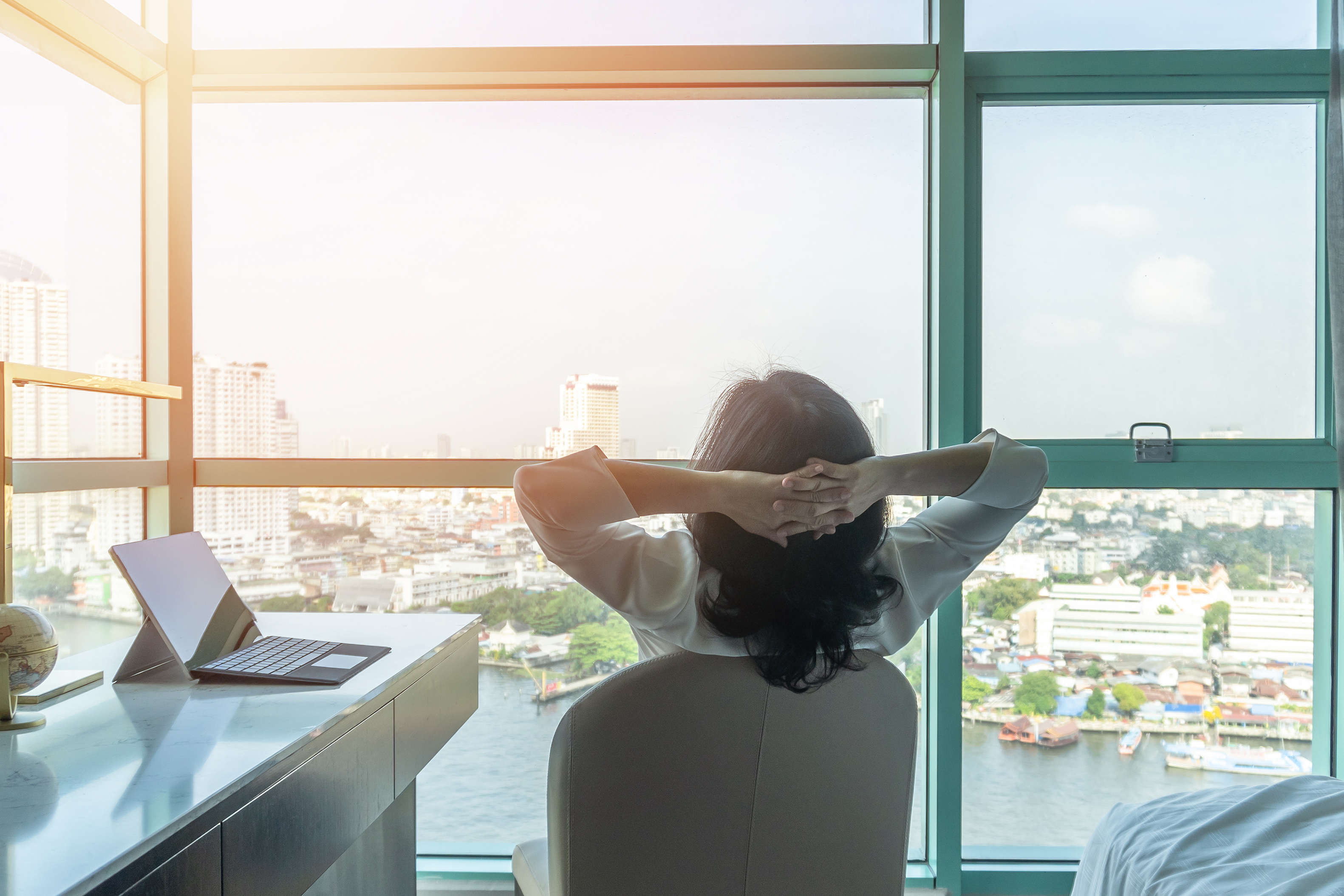 A woman relaxes in an office chair while looking out the window