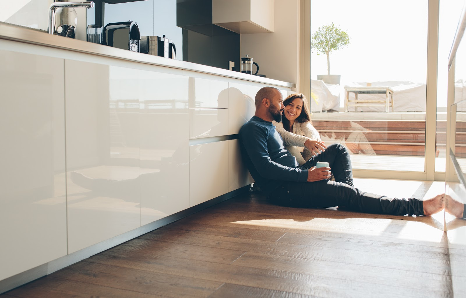 A couple sitting on the floor in their kitchen