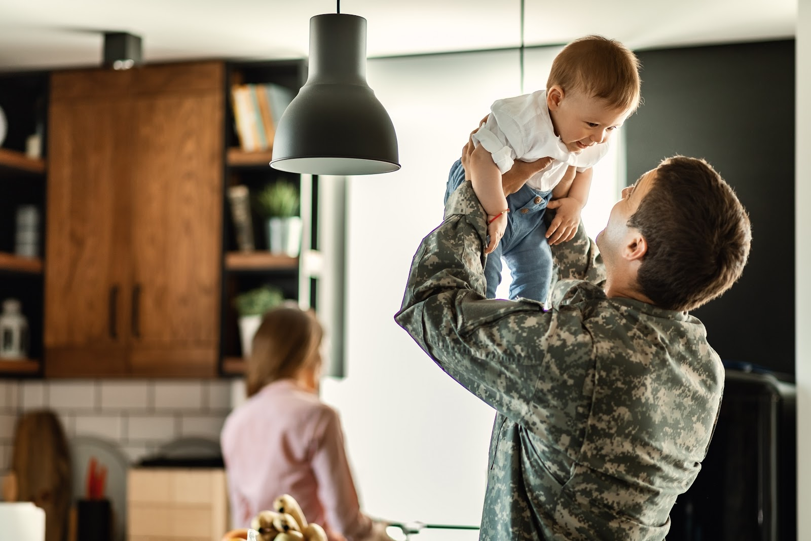 A military dad lifts his smiling baby boy in the air