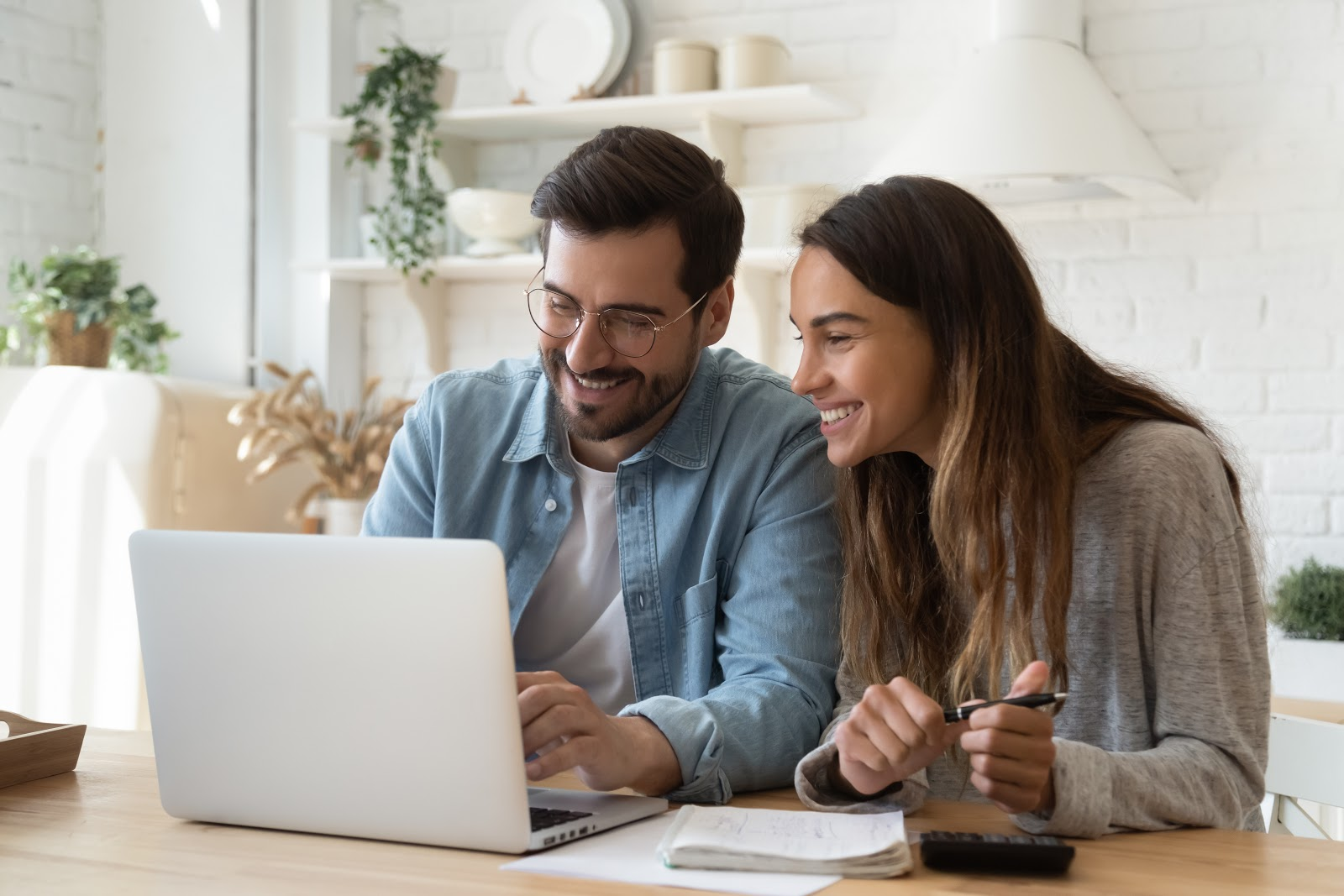 A smiling couple prepares taxes on a laptop
