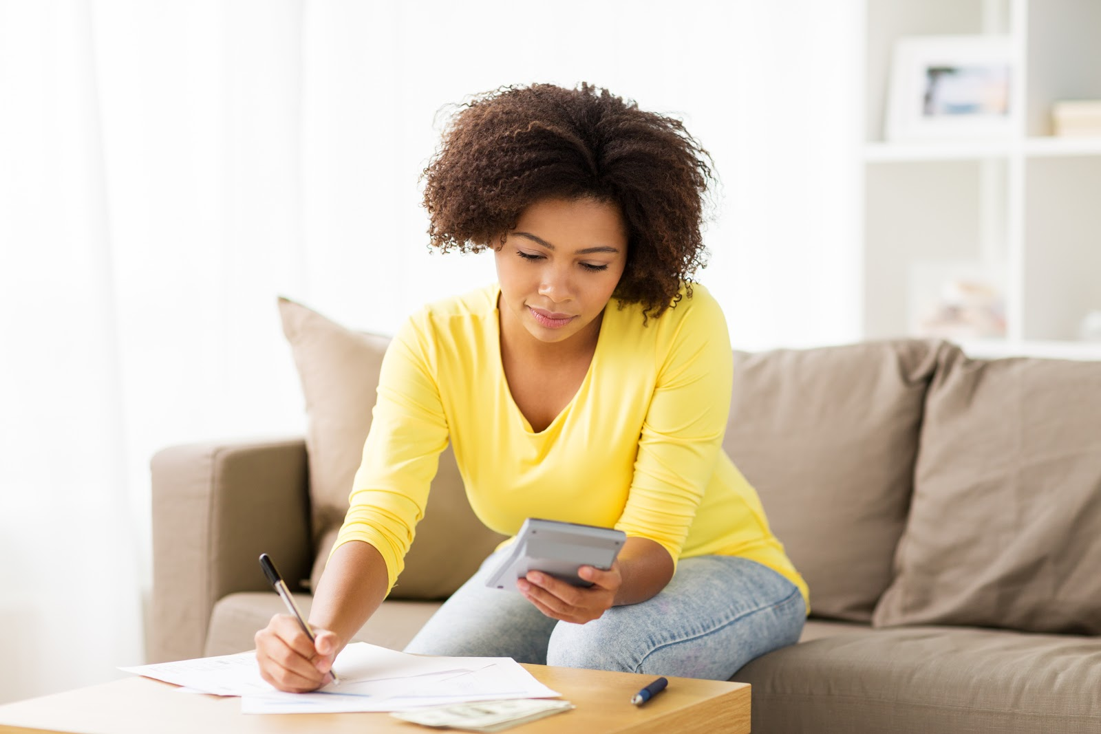How to become debt-free: A woman uses a calculator and sets a budget
