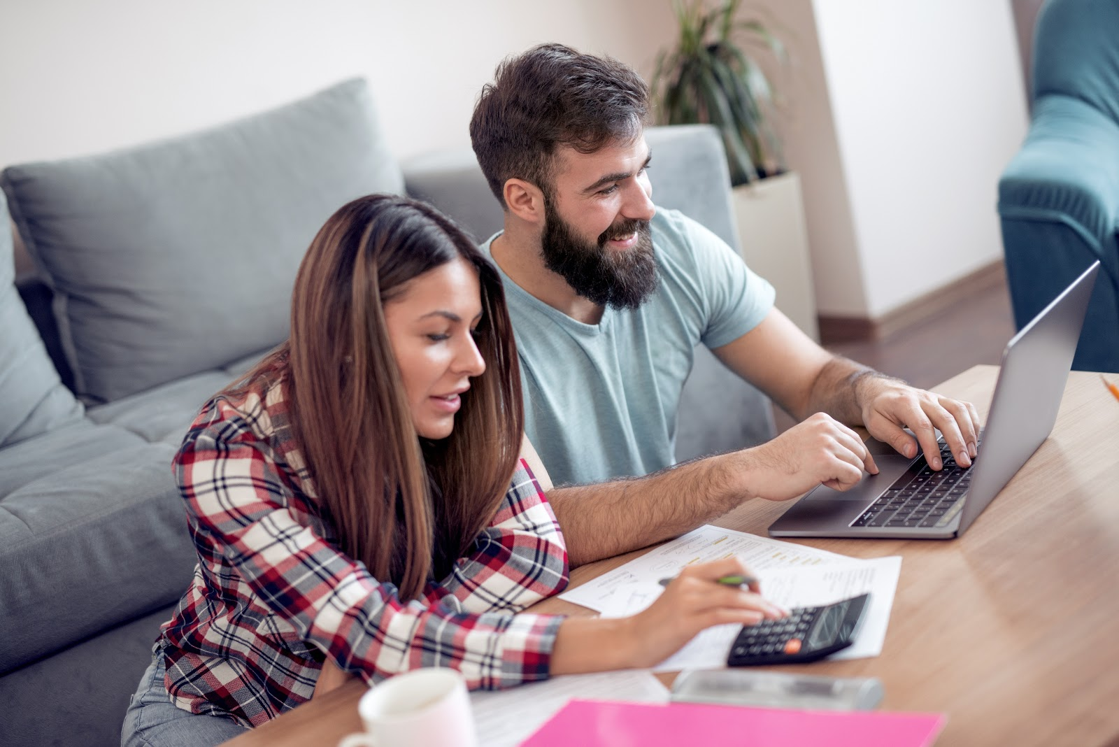 How to become debt-free: A couple uses a calculator and laptop to review their finances