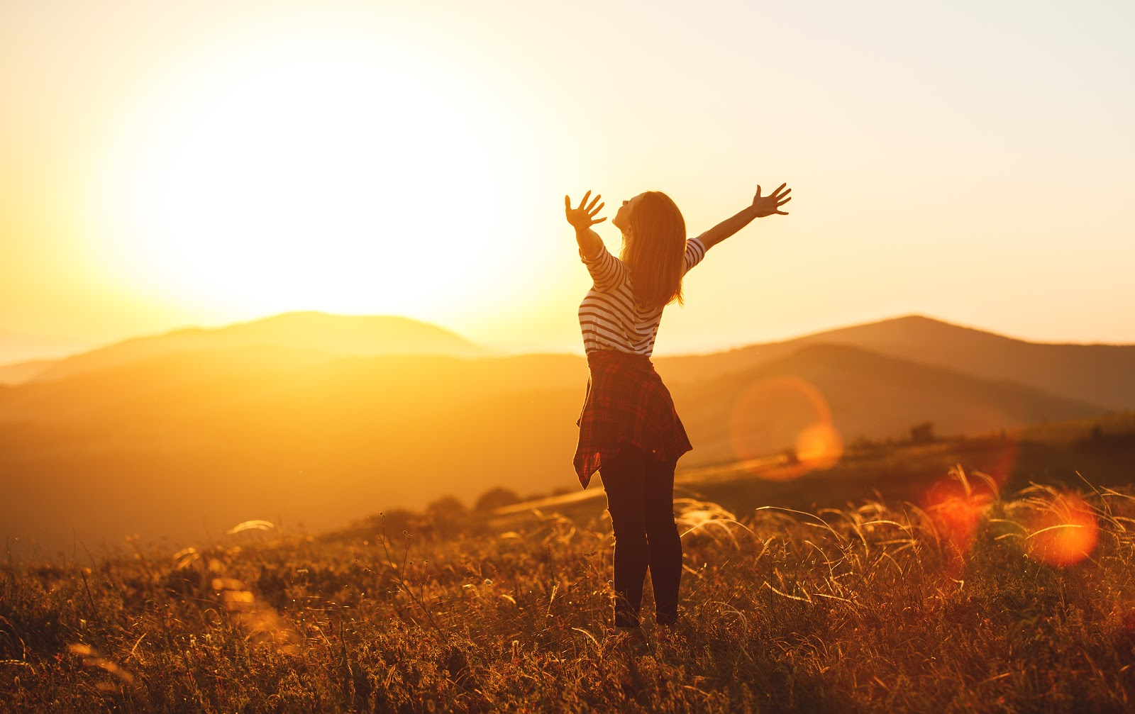 A woman raises her arms in the air while looking at a sunset