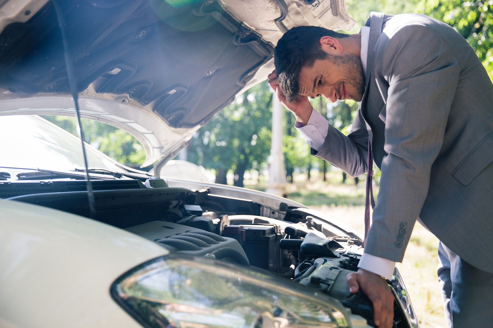 A man in a suit looks under the hood of a broken down car
