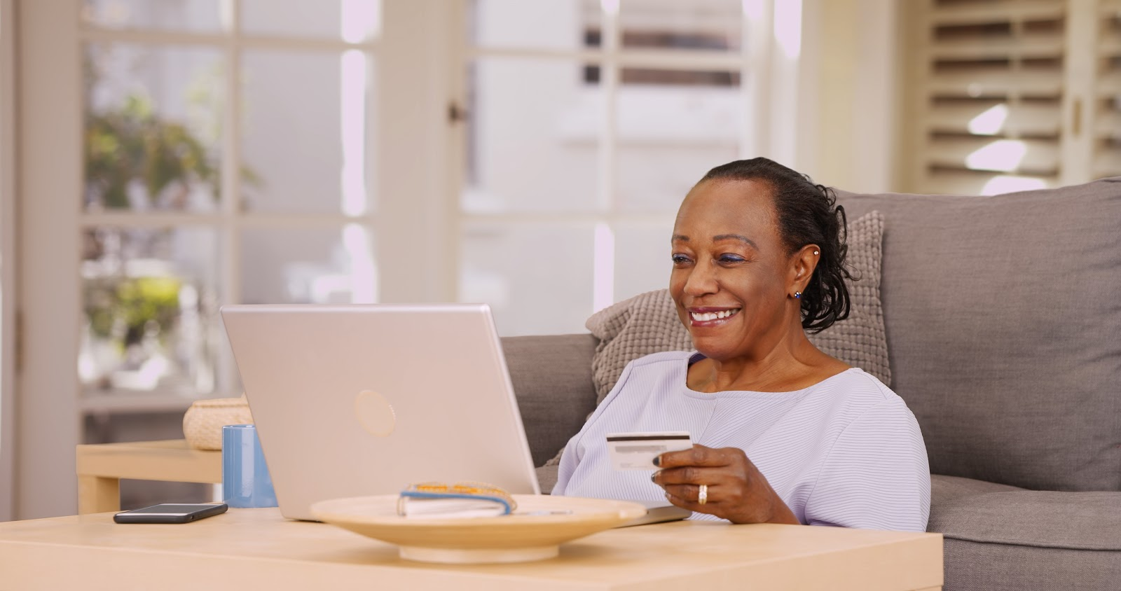 A smiling woman holds a credit card while looking at her laptop